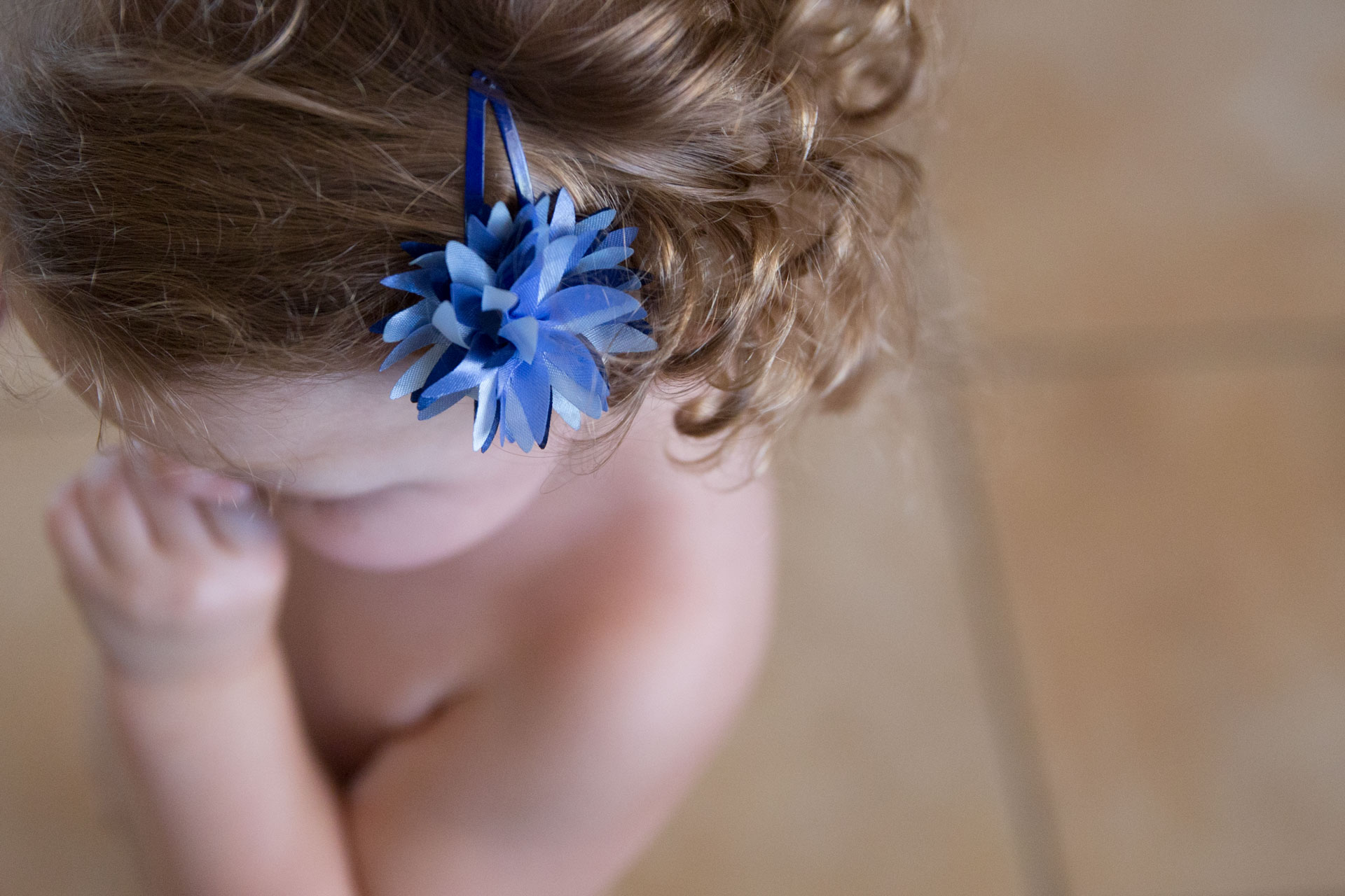Look frump above young toddlers hair with a bow in it and really tight curly hair