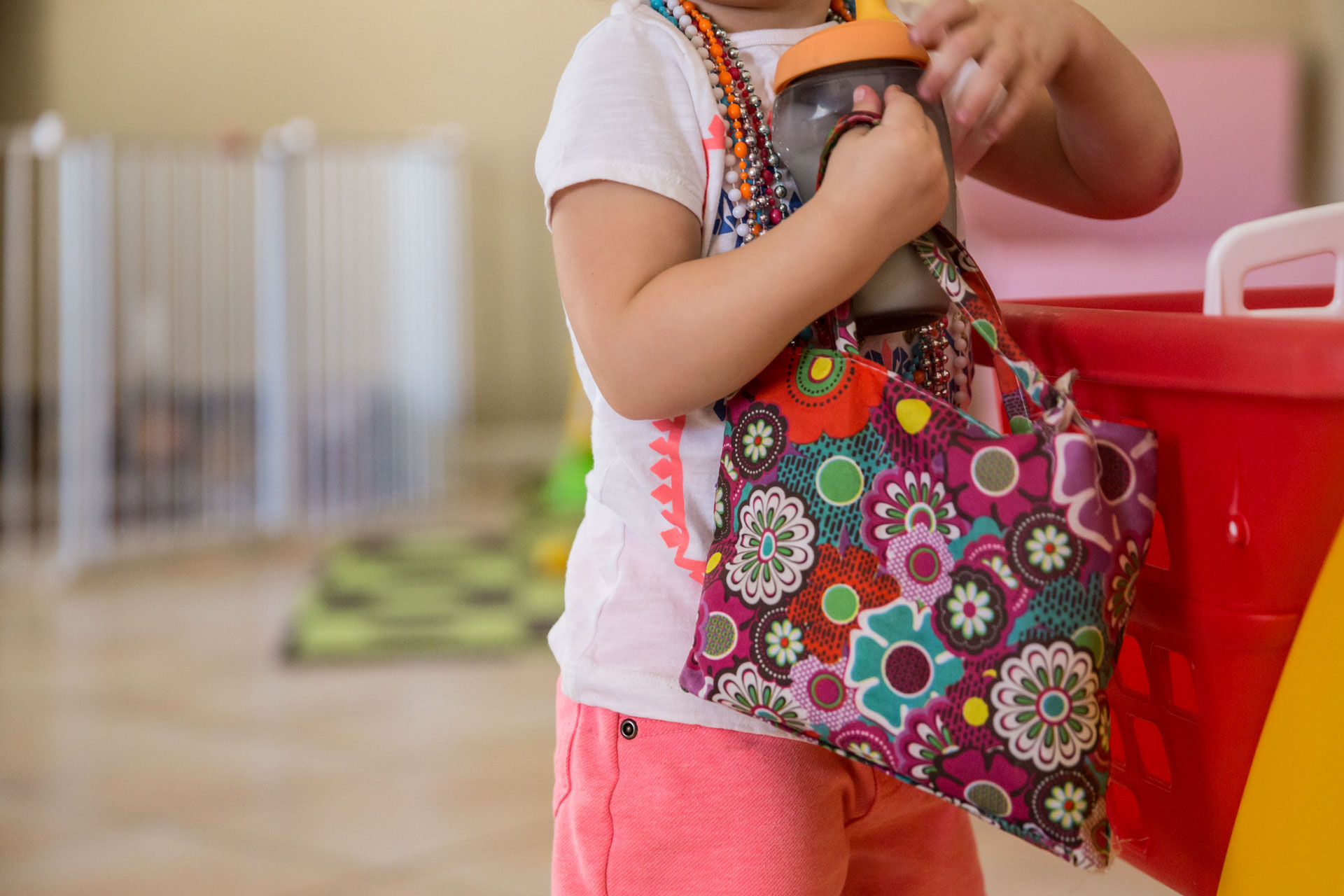 Toddler standing along next to her toy shopping cart with a purse and lots of necklaces on