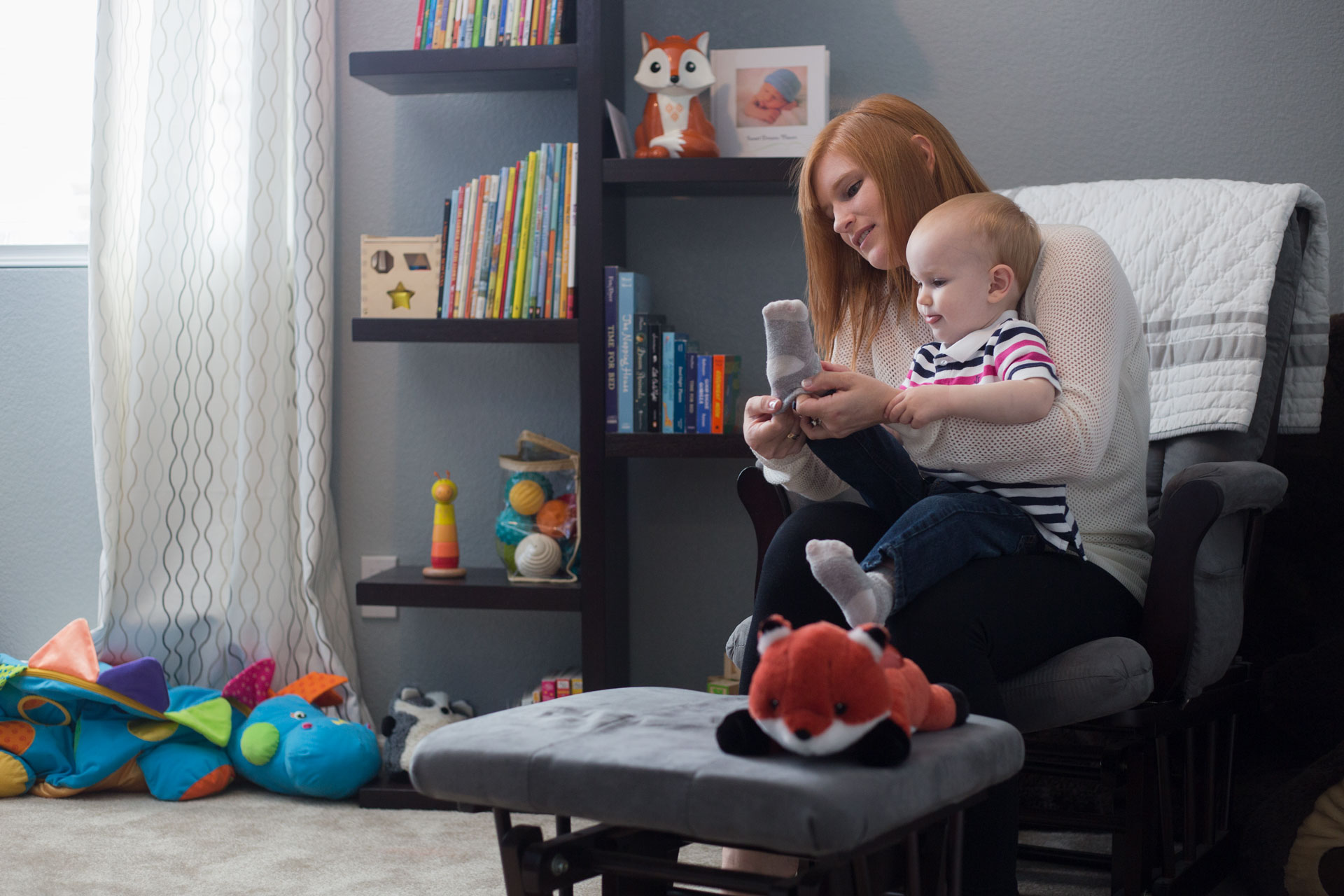 mom sitting in rocking chair with toddler as she puts on his sock