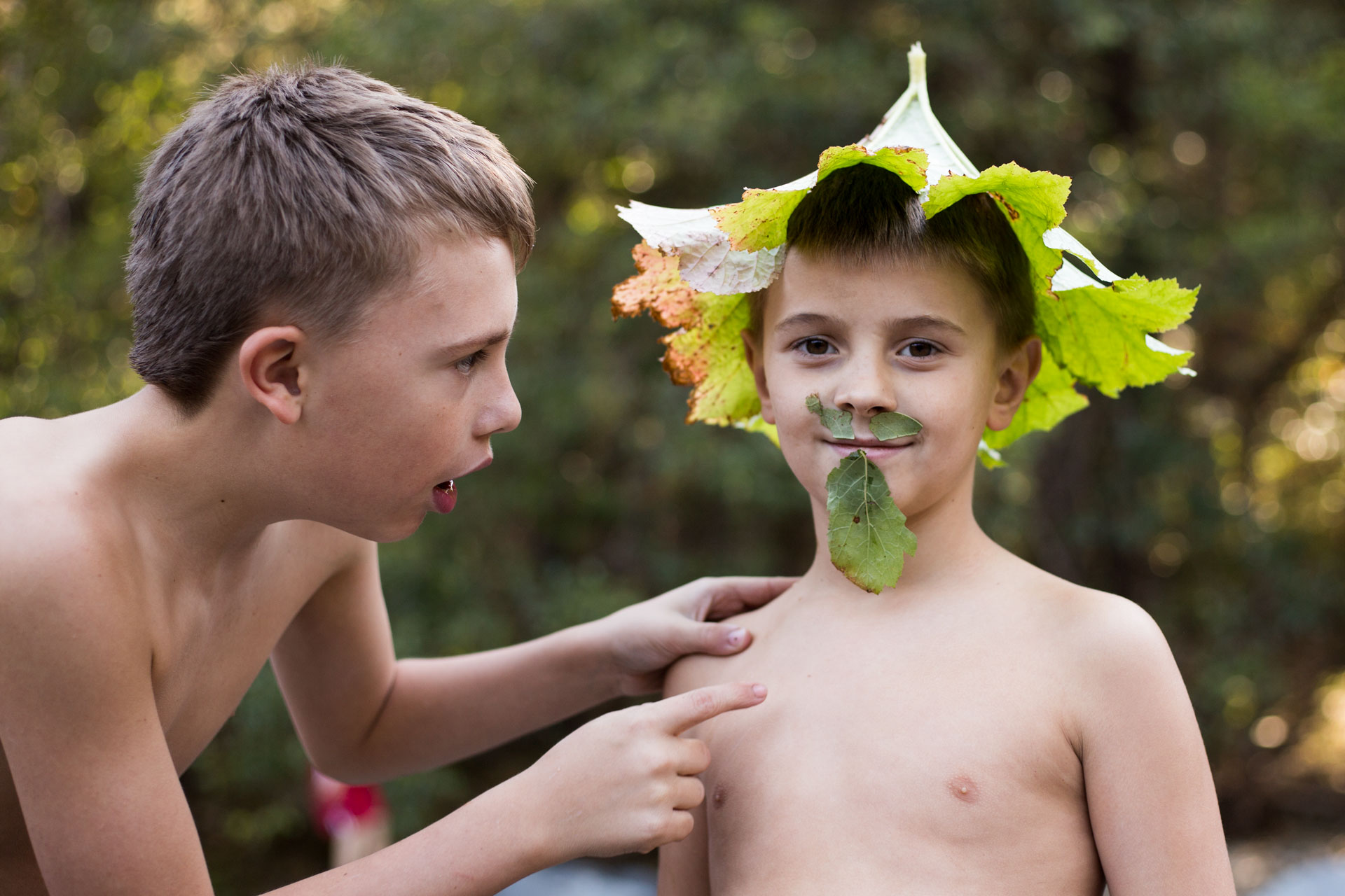 Boy with leaf hat one and another boy looking and pointing at him