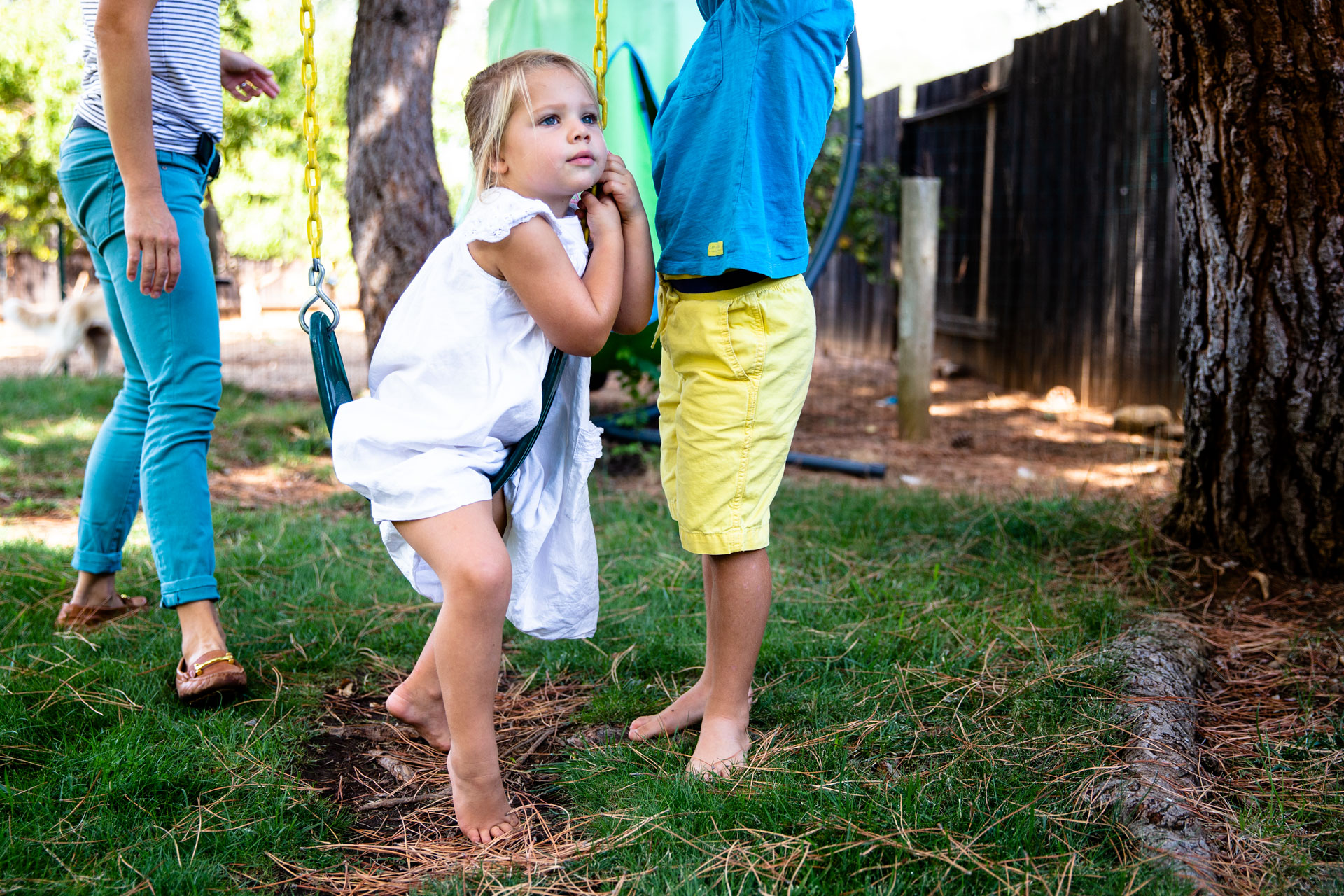 Kids playing in backyard and sister straddling swing
