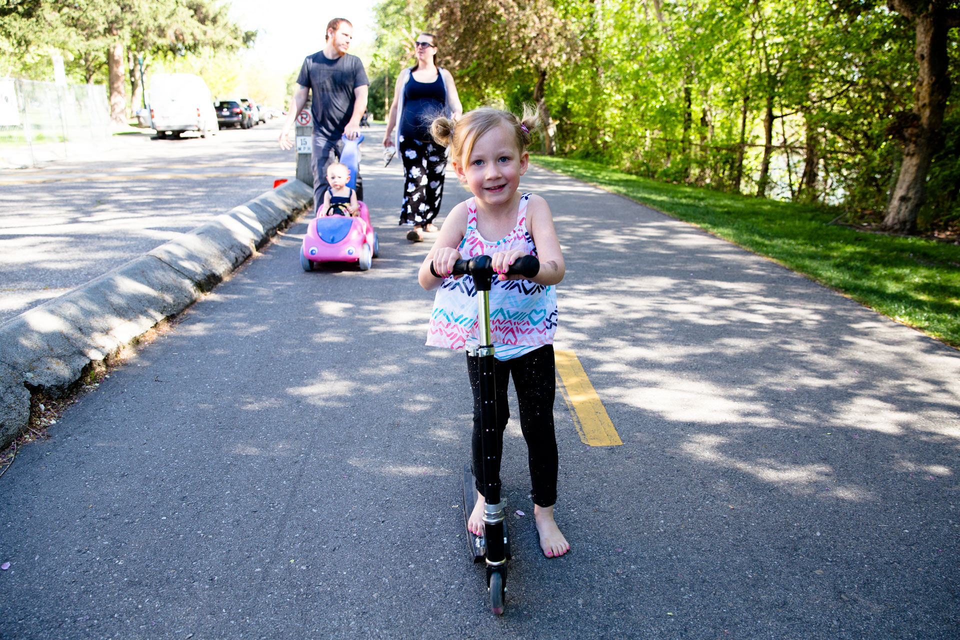 Girl riding scooter on the greenbelt while her parents push her sister in a car stroller behind her