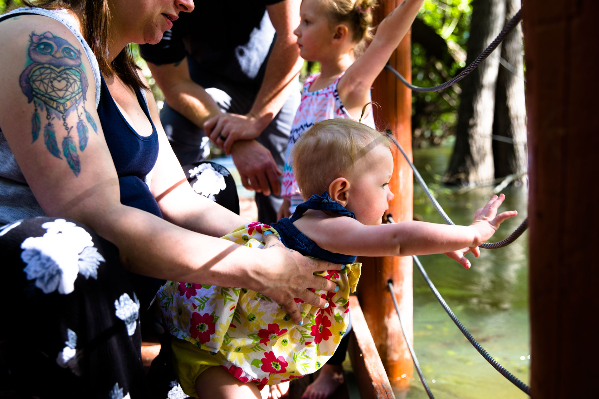 Sisters looking over the railing at the Boise River with parents holding on tight from behind