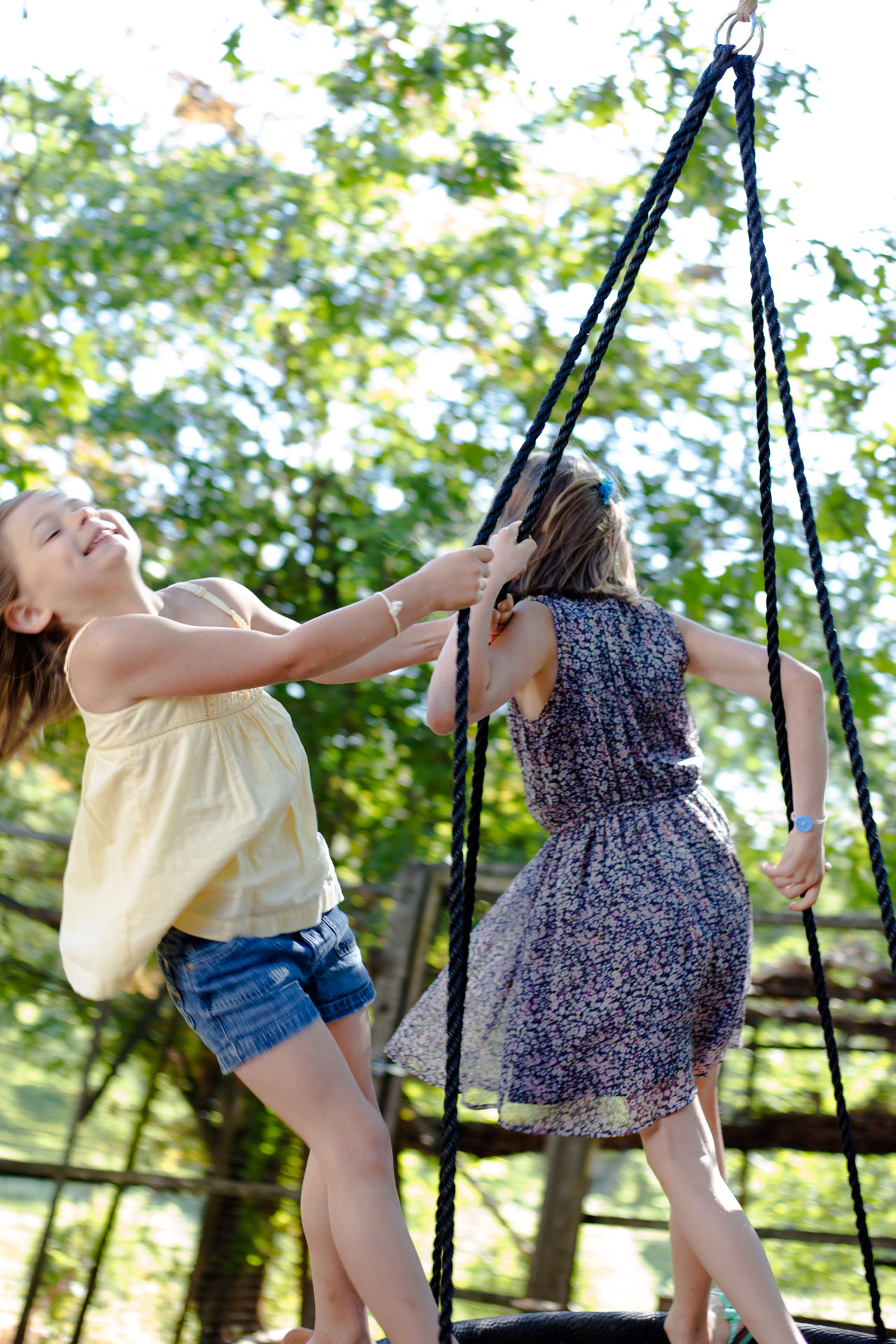 two sisters swinging together on net swing with green trees behind them and smiling