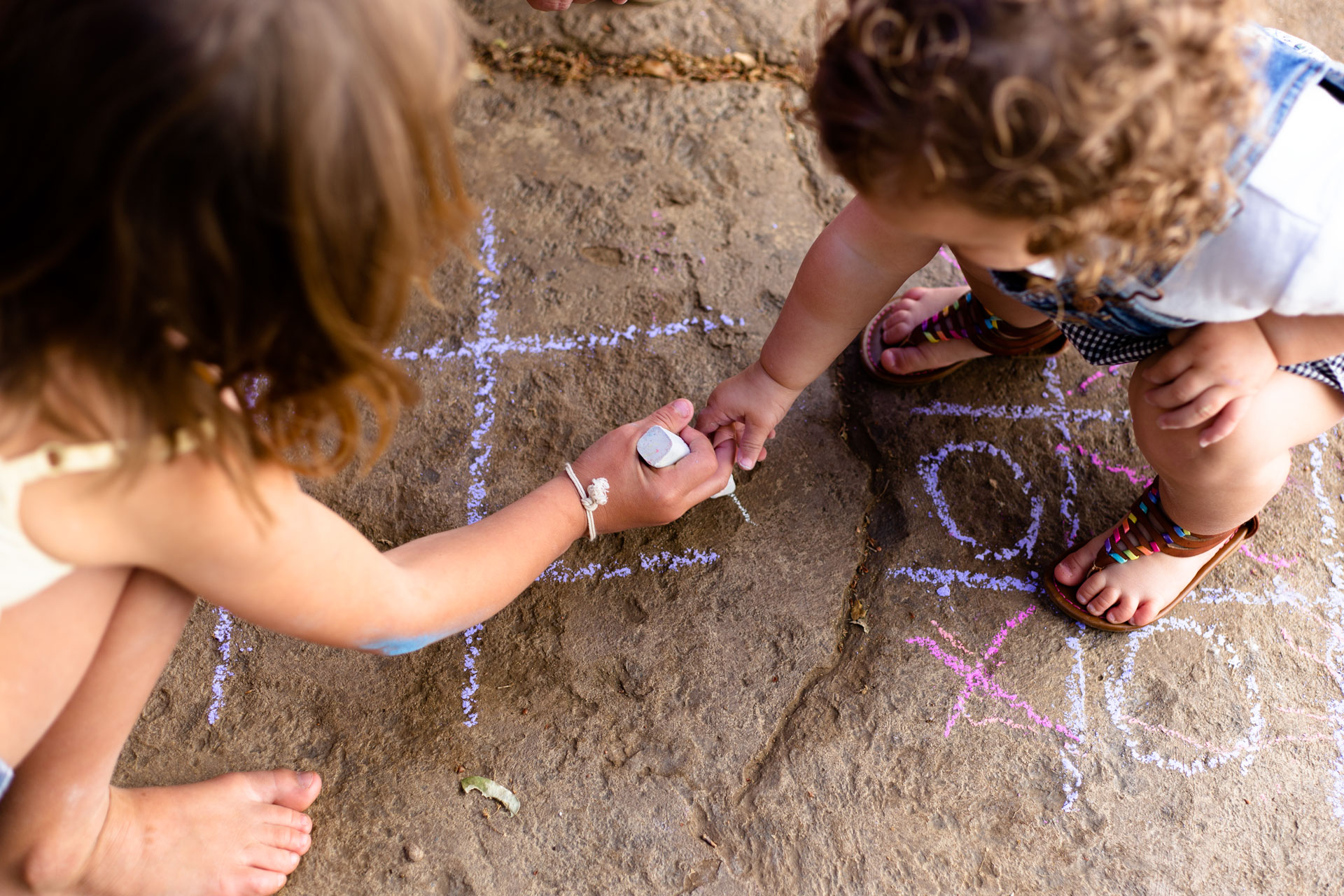 two sisters playing tic tac toe with chalk on the sidewalk outside their home