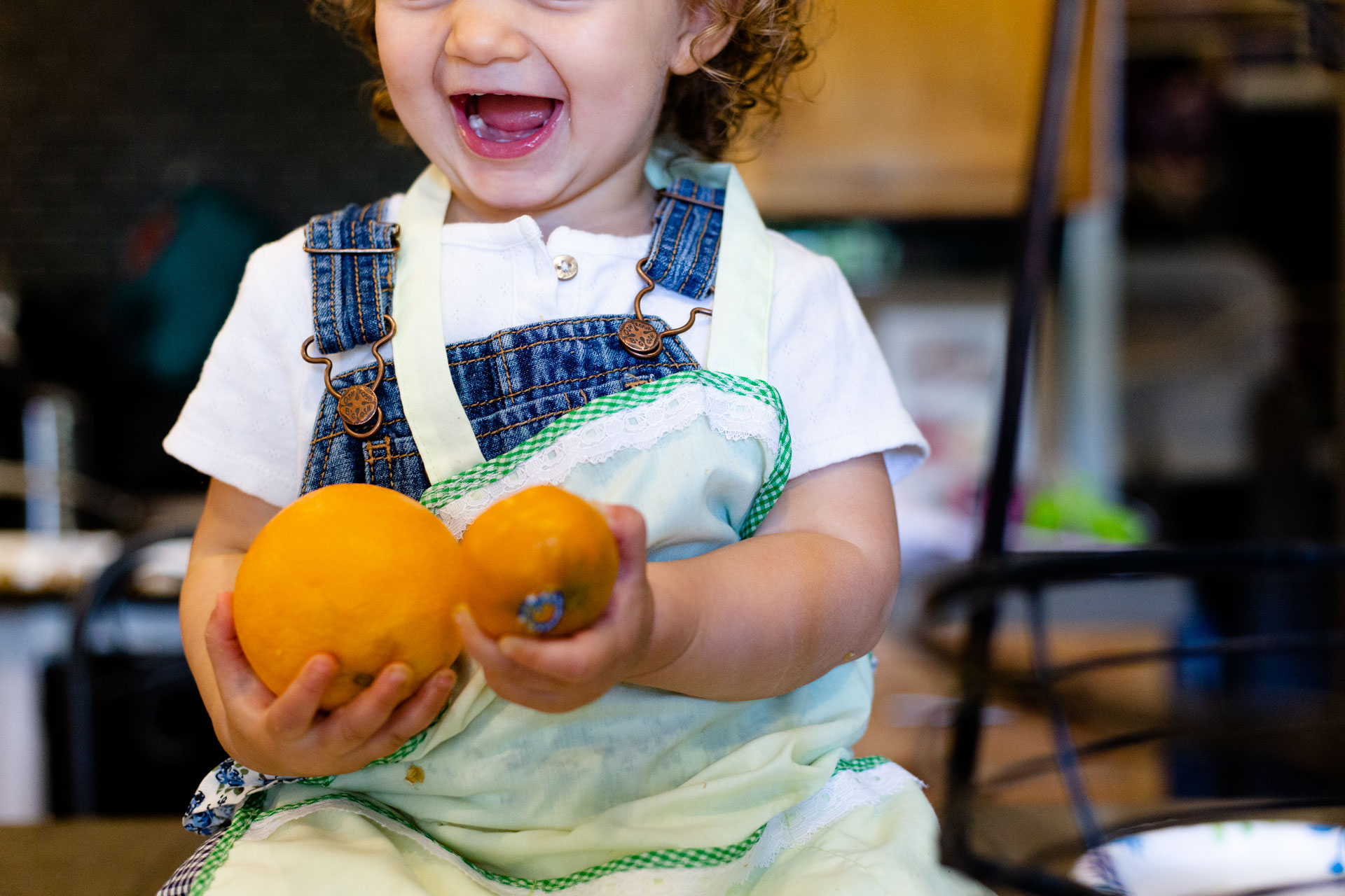 Small toddler holding oranges while sitting down on counter in family kitchen