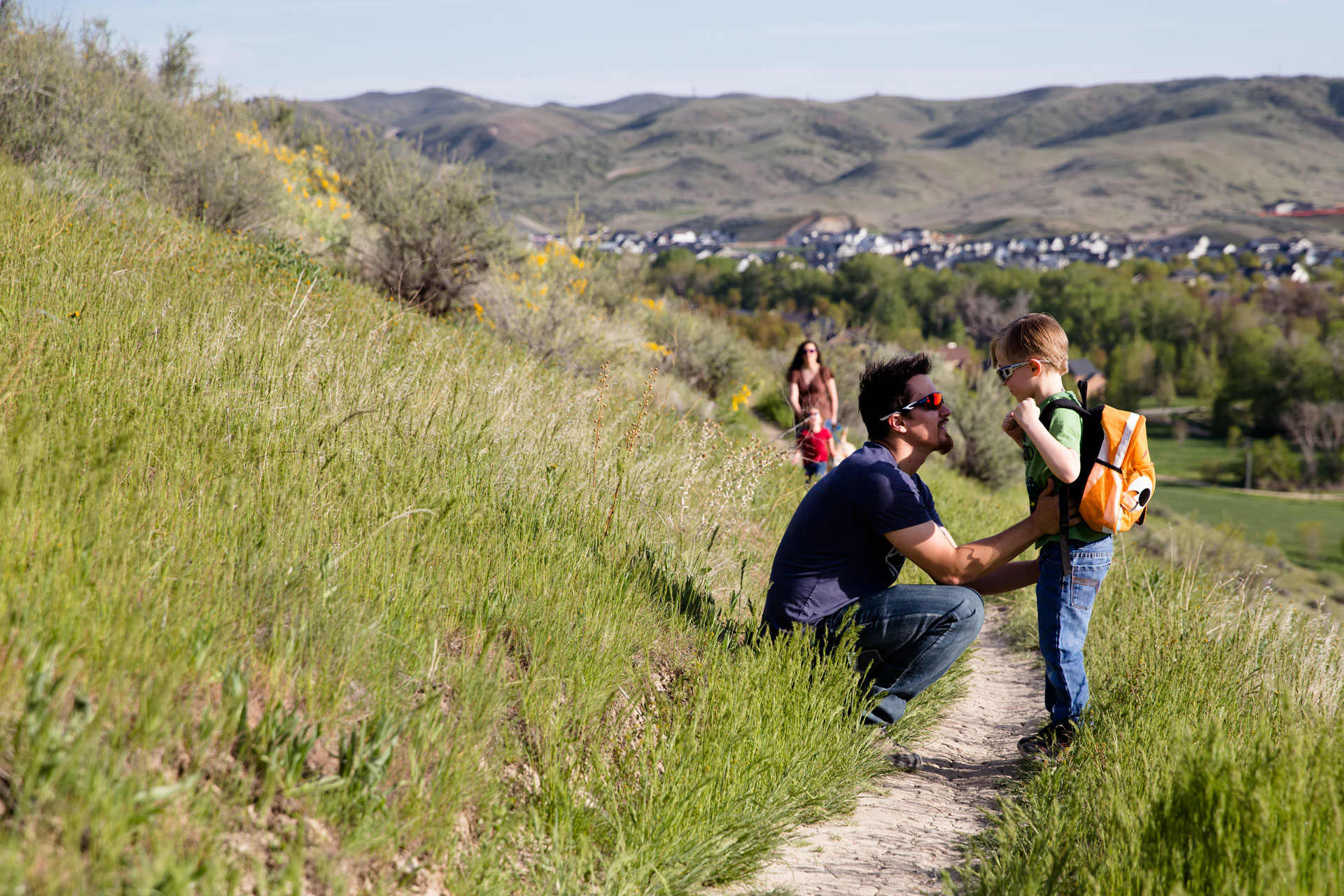dad kneeling down to talk with youngest son on hike with family on a sunny day