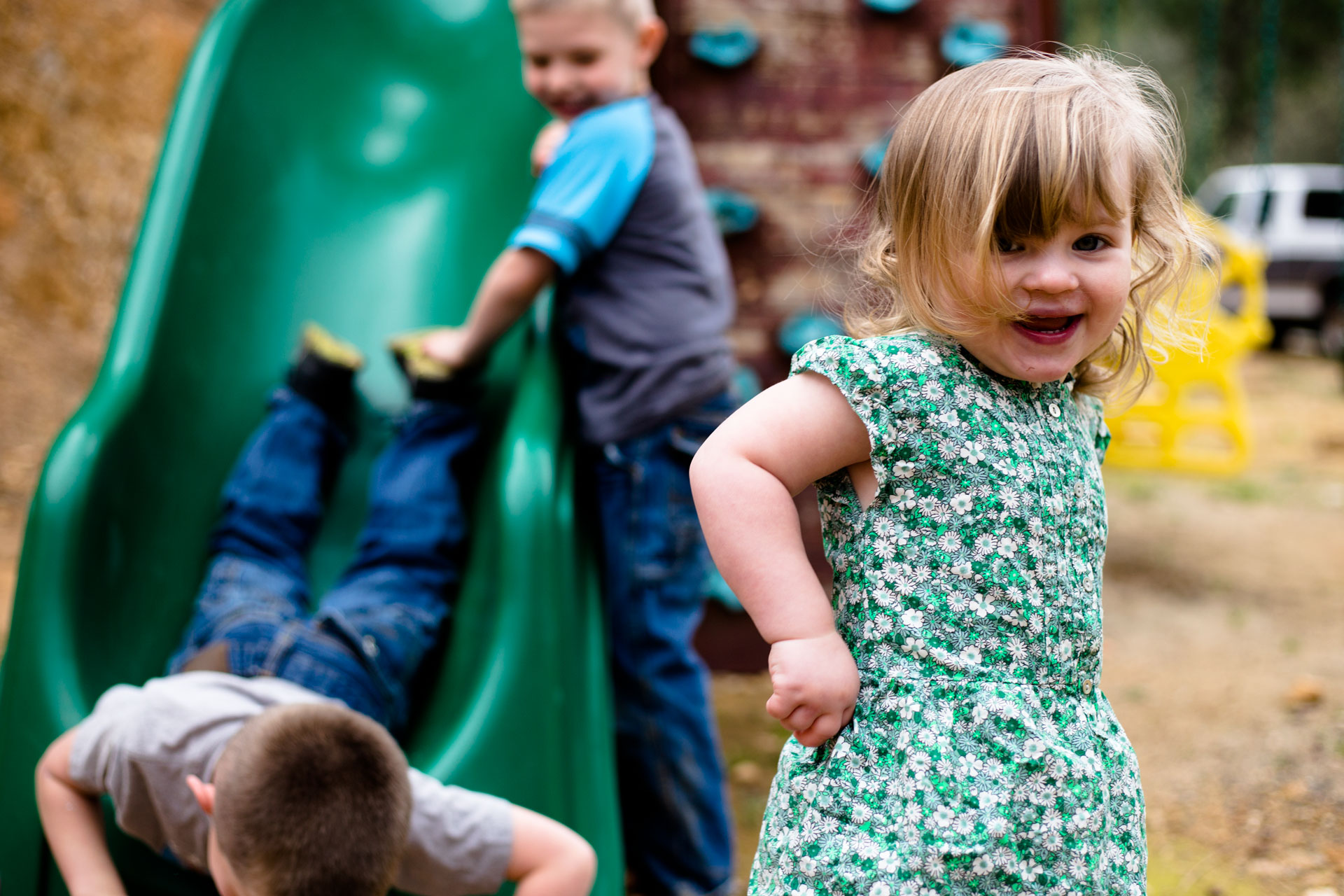 Little sister just coming off the slide while brothers are close behind laughing and smiling