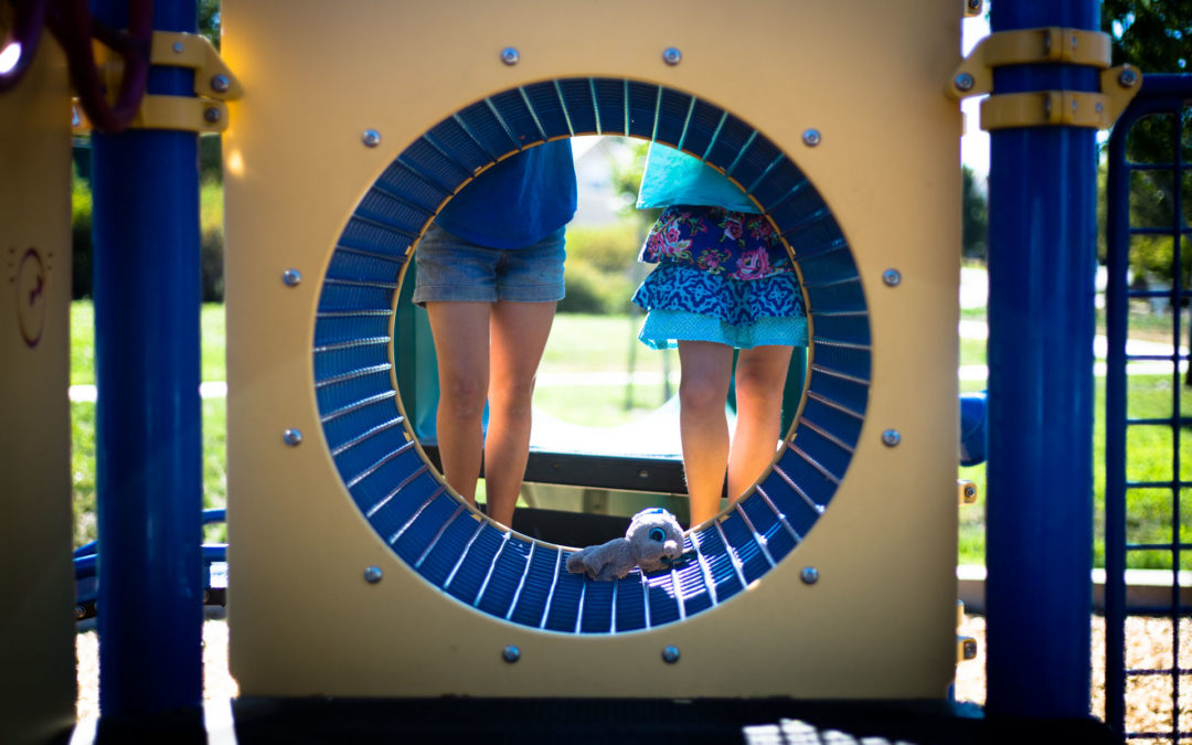 Two girls standing wbehind a circle tunnel play ground structure with a stuffed animal in the middle of the tunnel