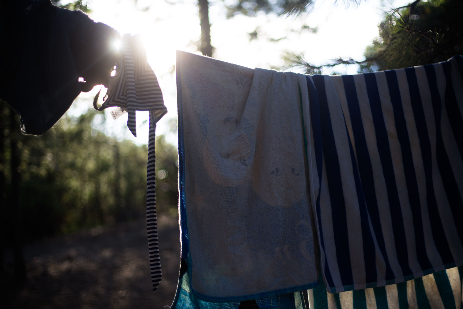 Towels and swimming suit laying the line with the sun peeking behind them