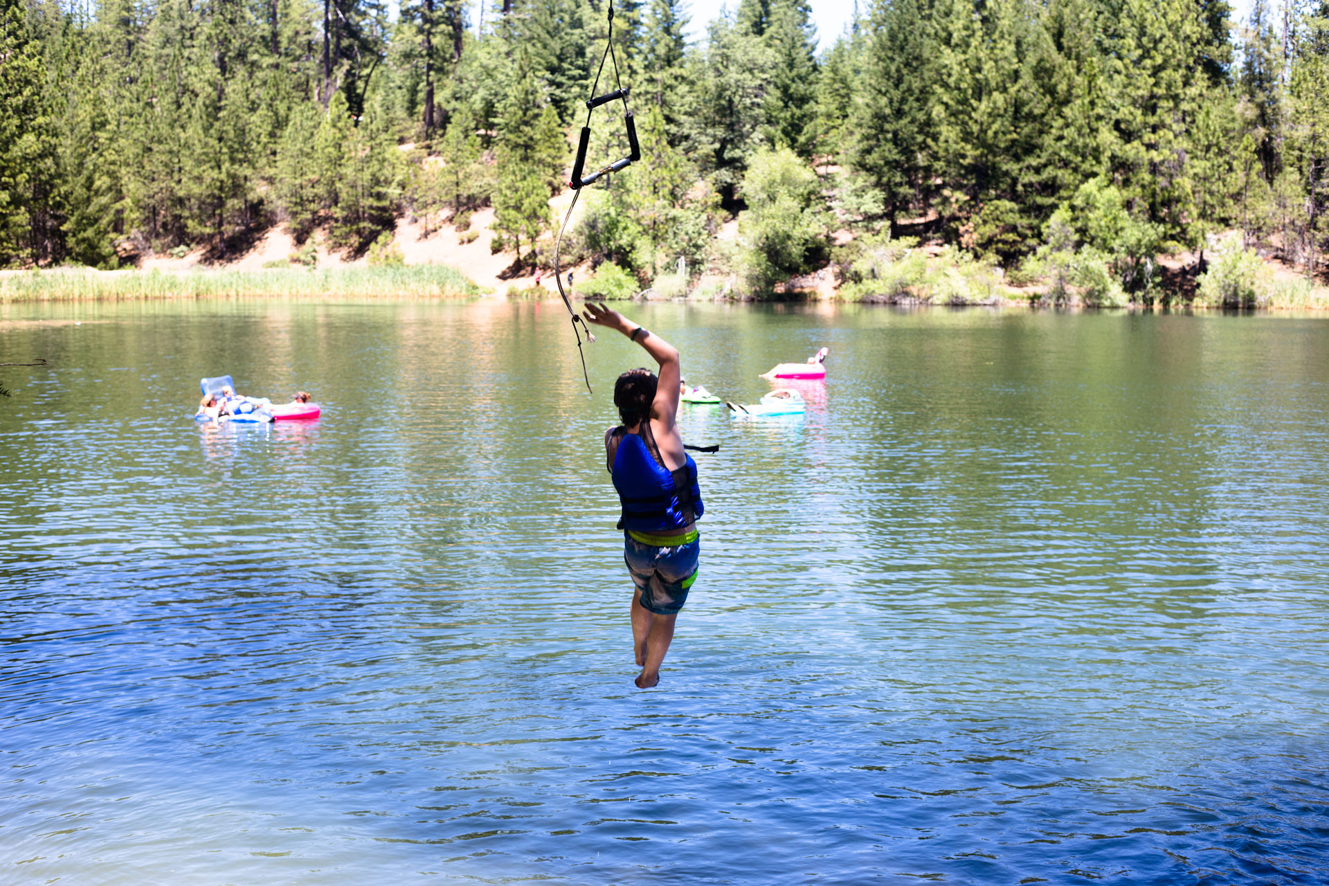 view from behind of boy flying from a rope swing into the lake