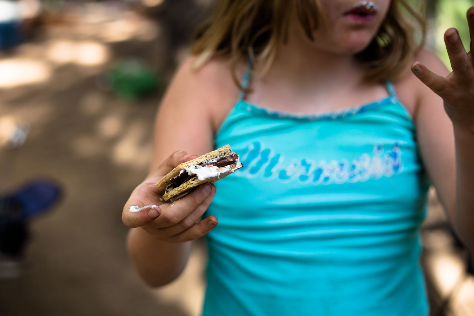 up close young girl holding a s'more and wearing a swimming suit