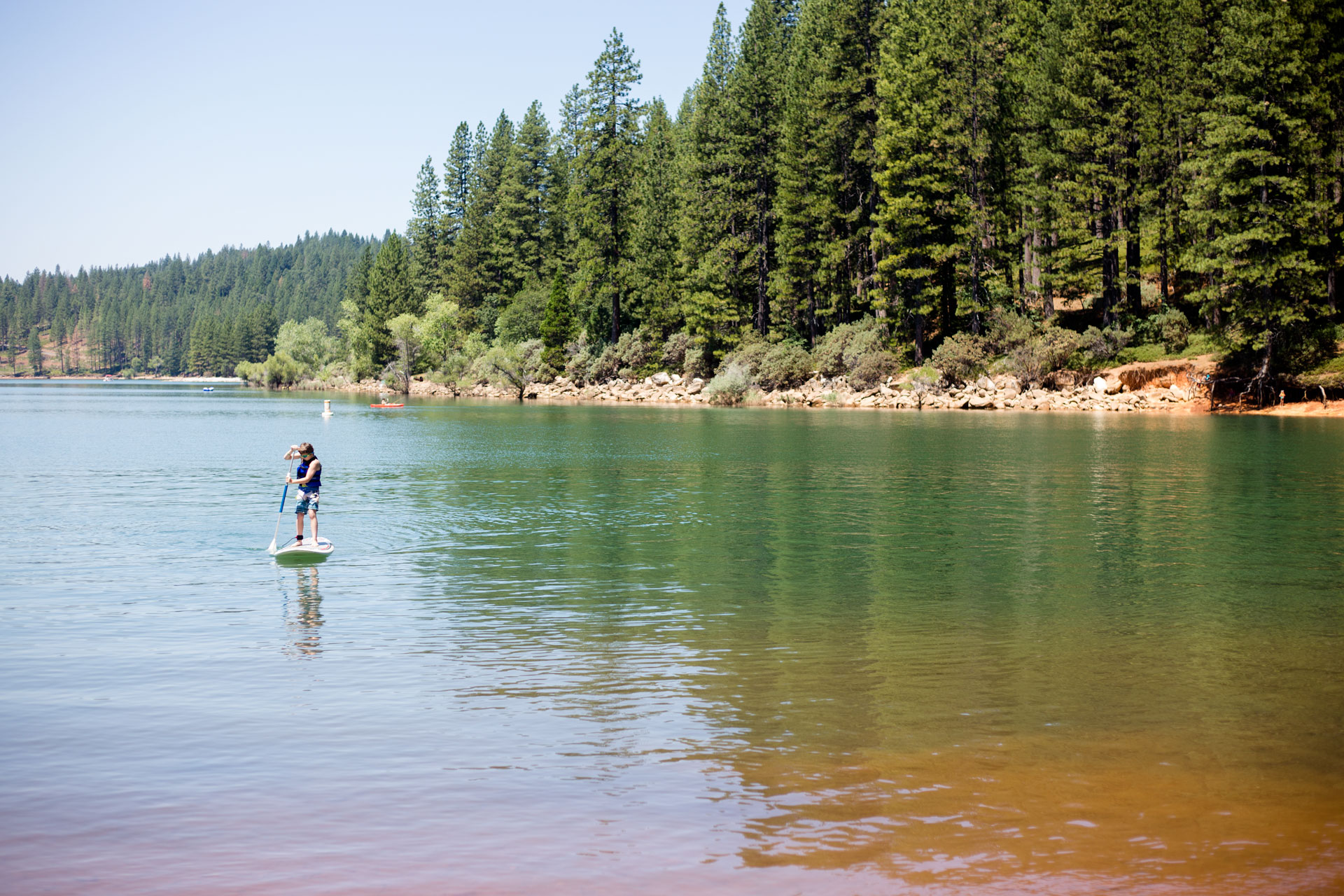 boy paddle boarding on the lake with pine trees lining the lake behind him