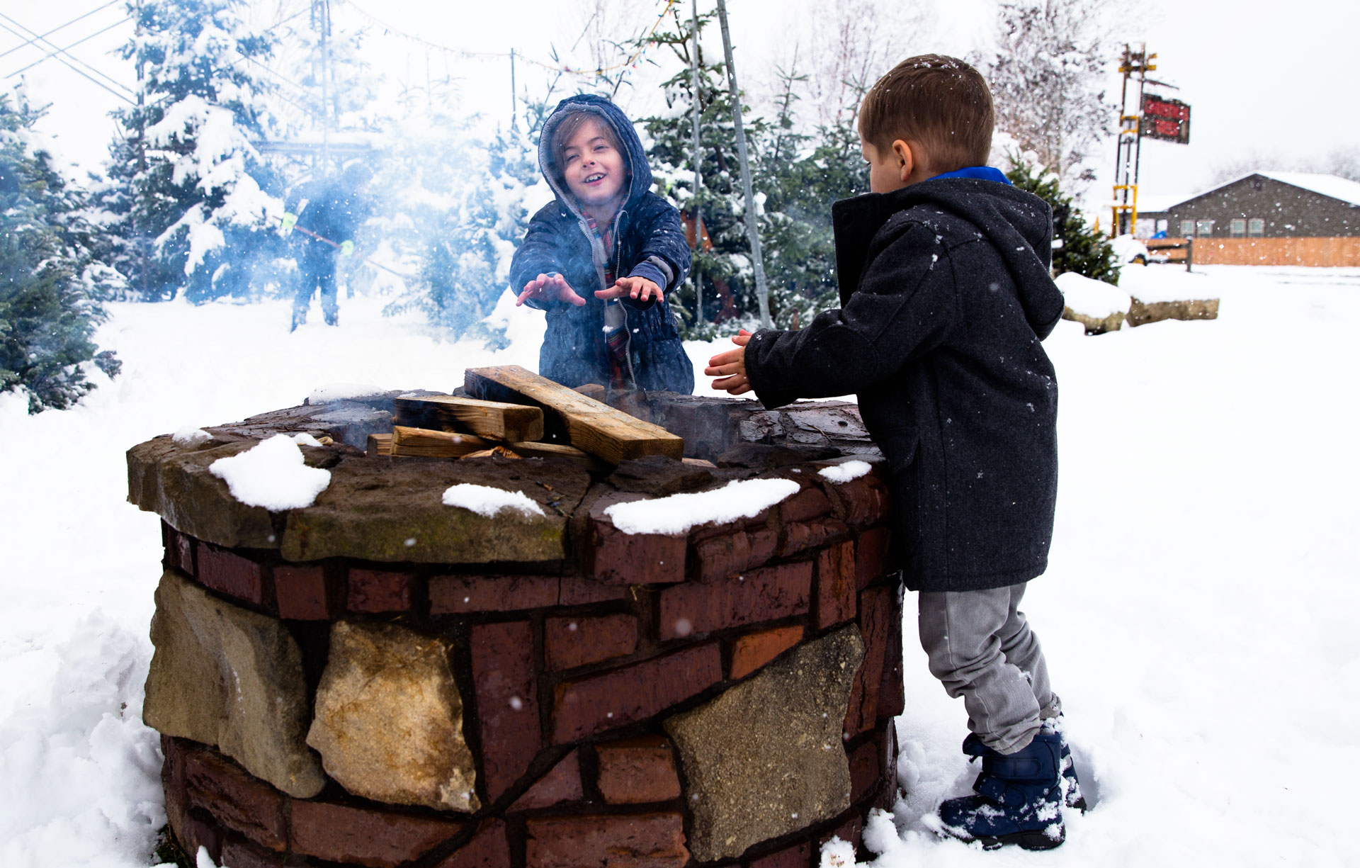 brother and sister putting hands by the fire to warm up as it snows around them