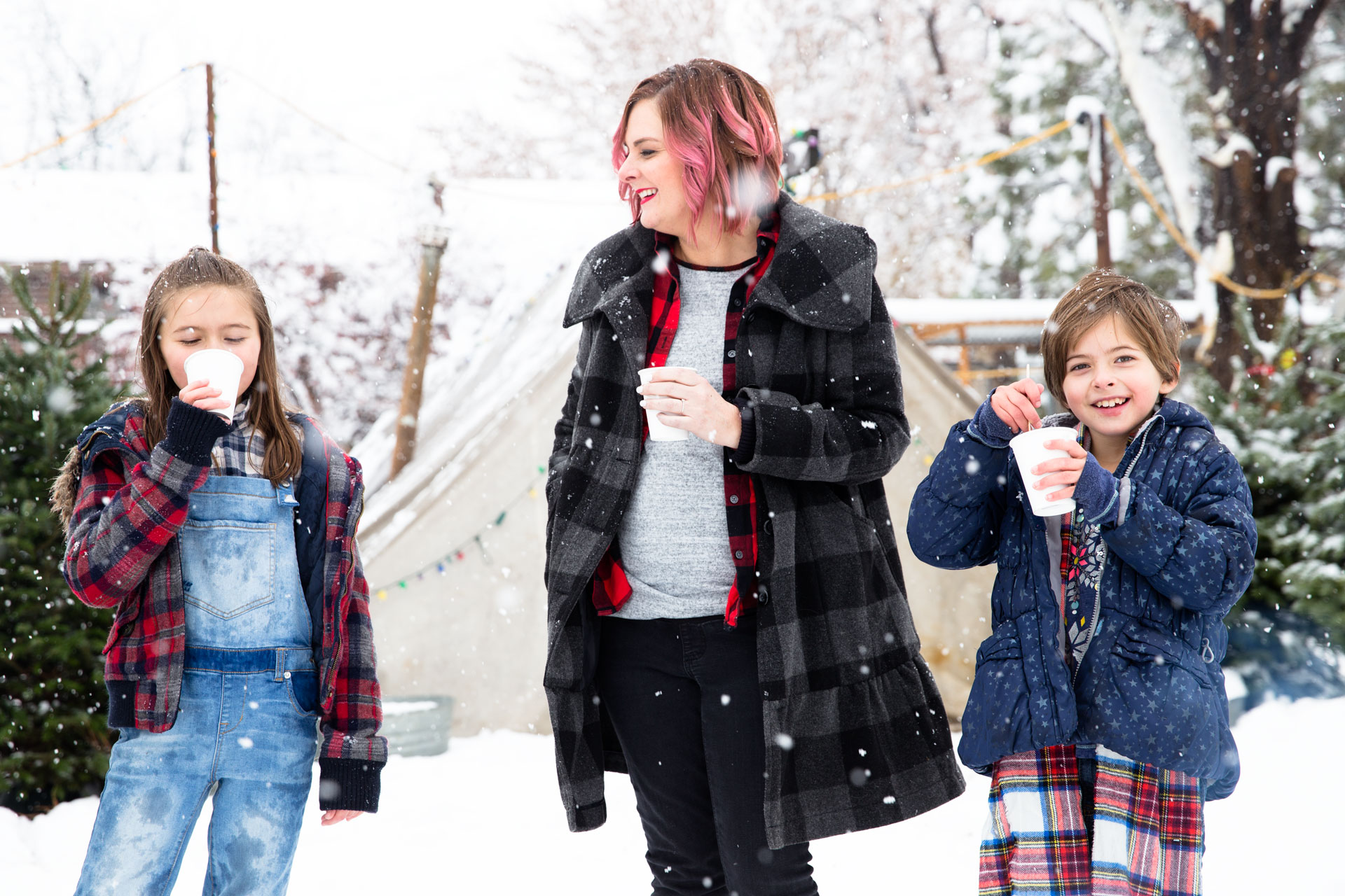 Mom and two daughters sipping hot chocolate while getting their Christmas tree at a farm and its snowing