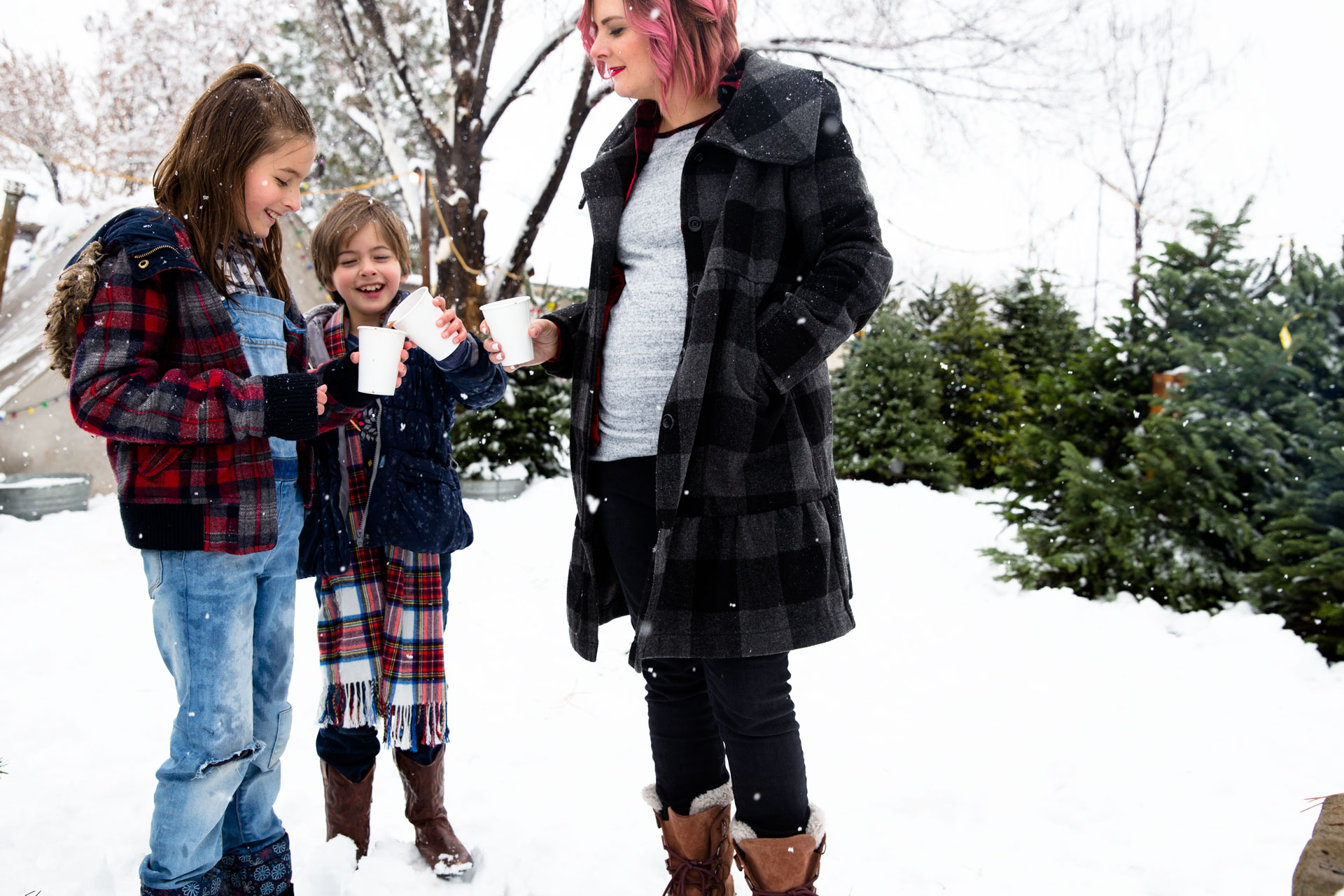 Mom and daughters drinking hot cocoa while they get their Christmas tree