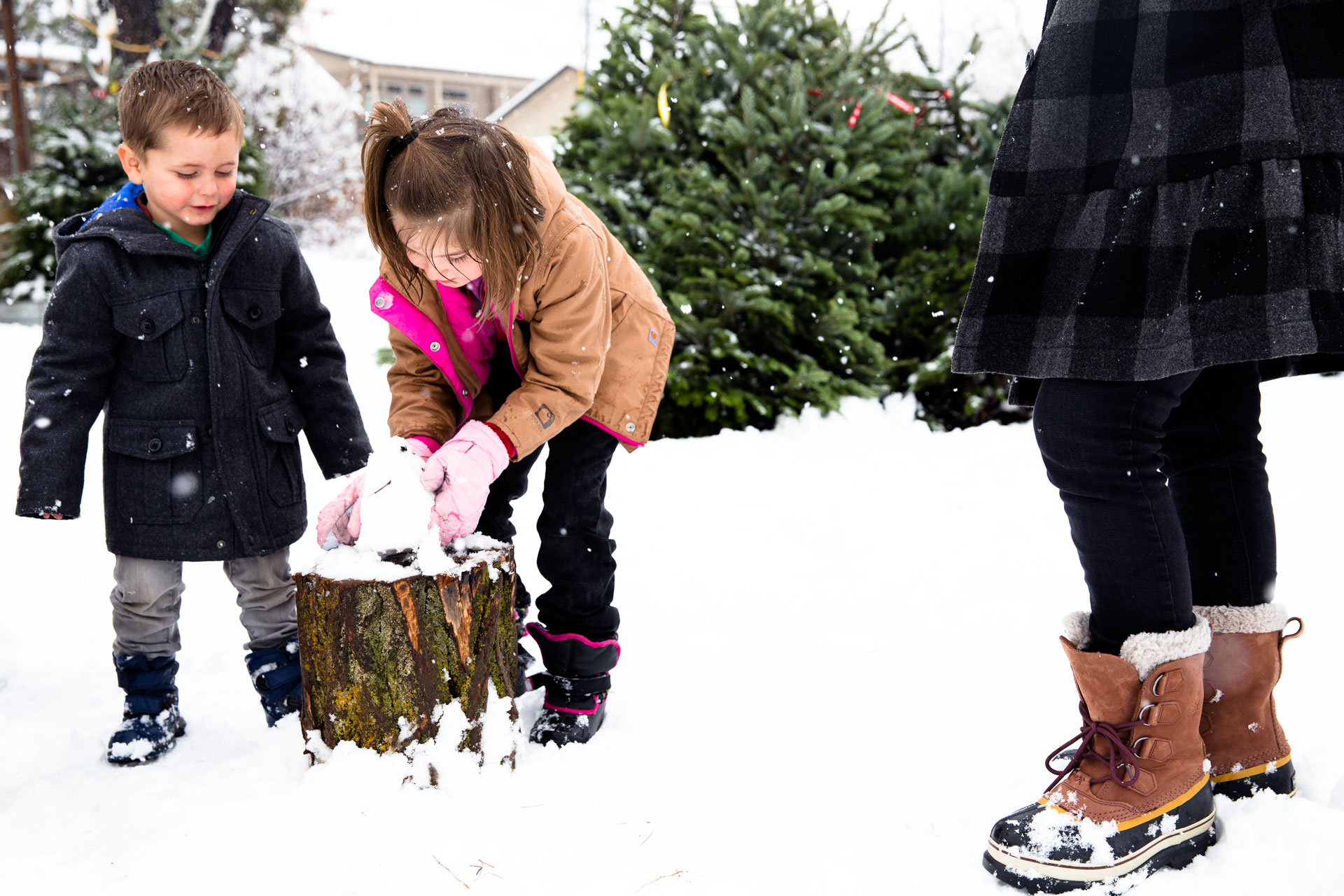 two kids building a small snow man while it snows and they are getting their Christmas Tree