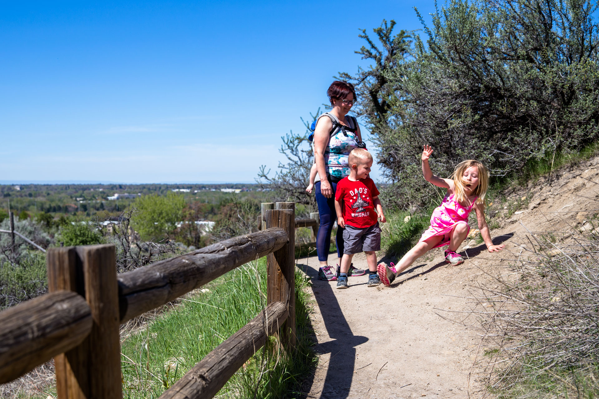 Mom and kids hiking up the trail over the city and daughter slipping on the dirt in surprise