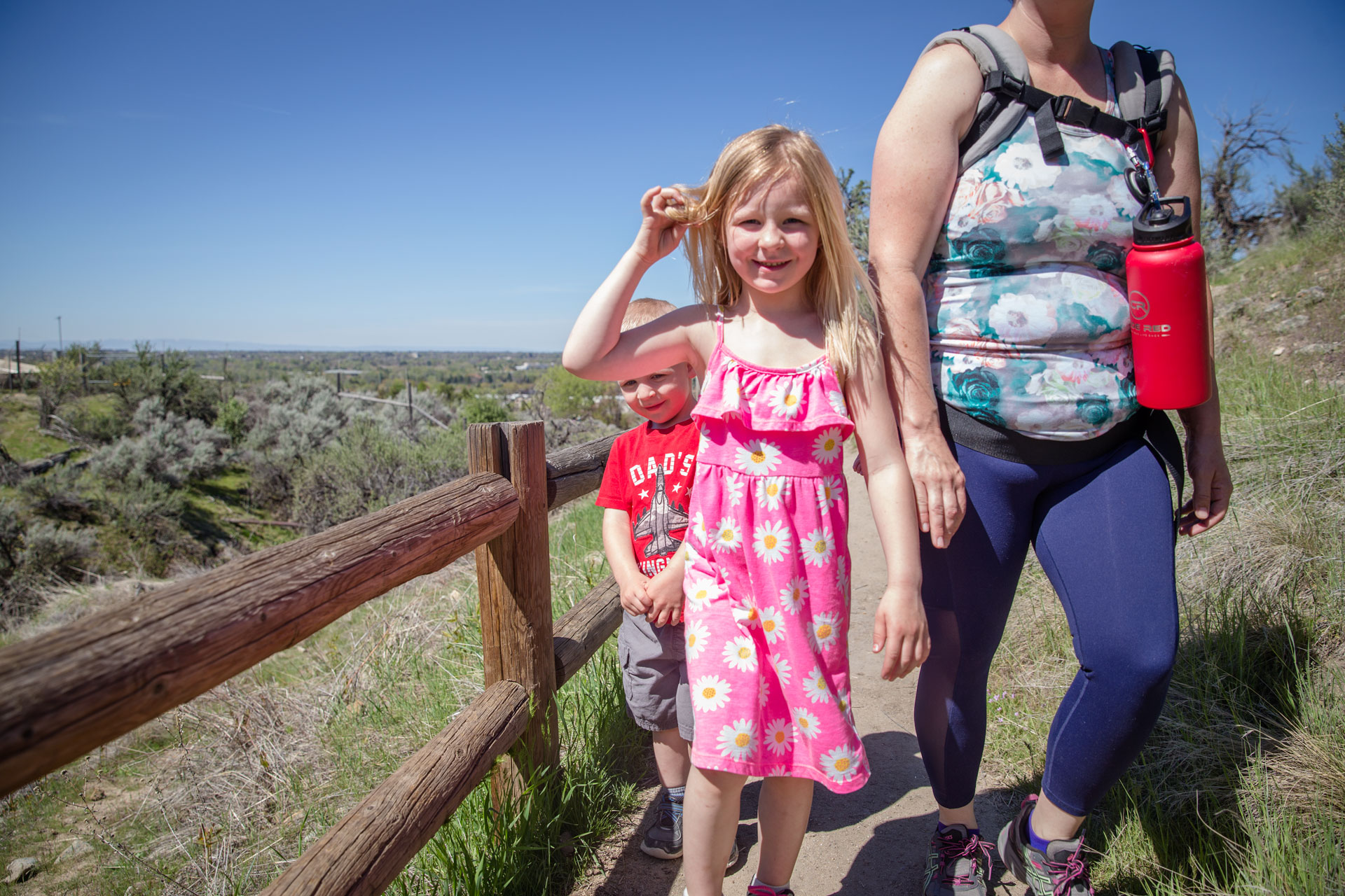 young girl twirling her hair as she climbs the mountain hike with her mom and brothers