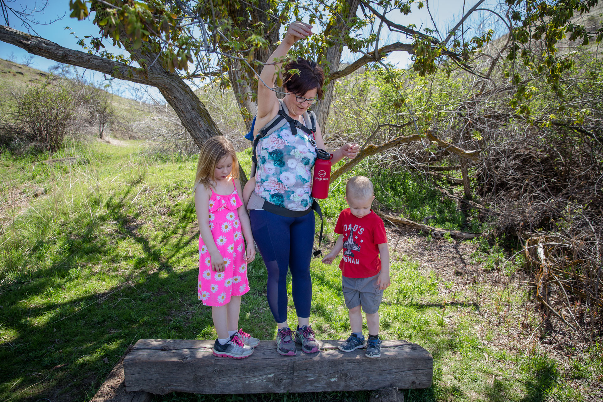 Mom and kids standing on bench while dropping a leaf fro a tree to see what it will do