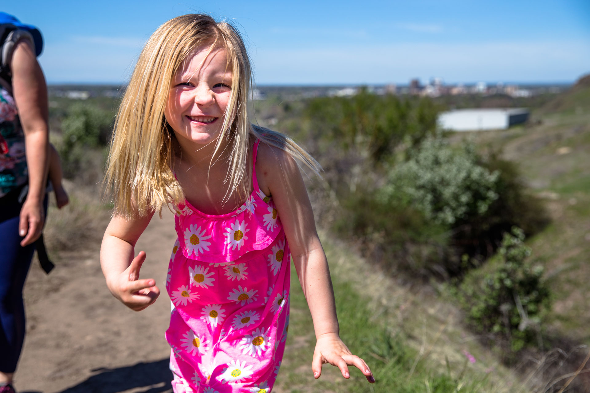 little girl looking at the camera and smiling as she walks up the hill on the steep trail