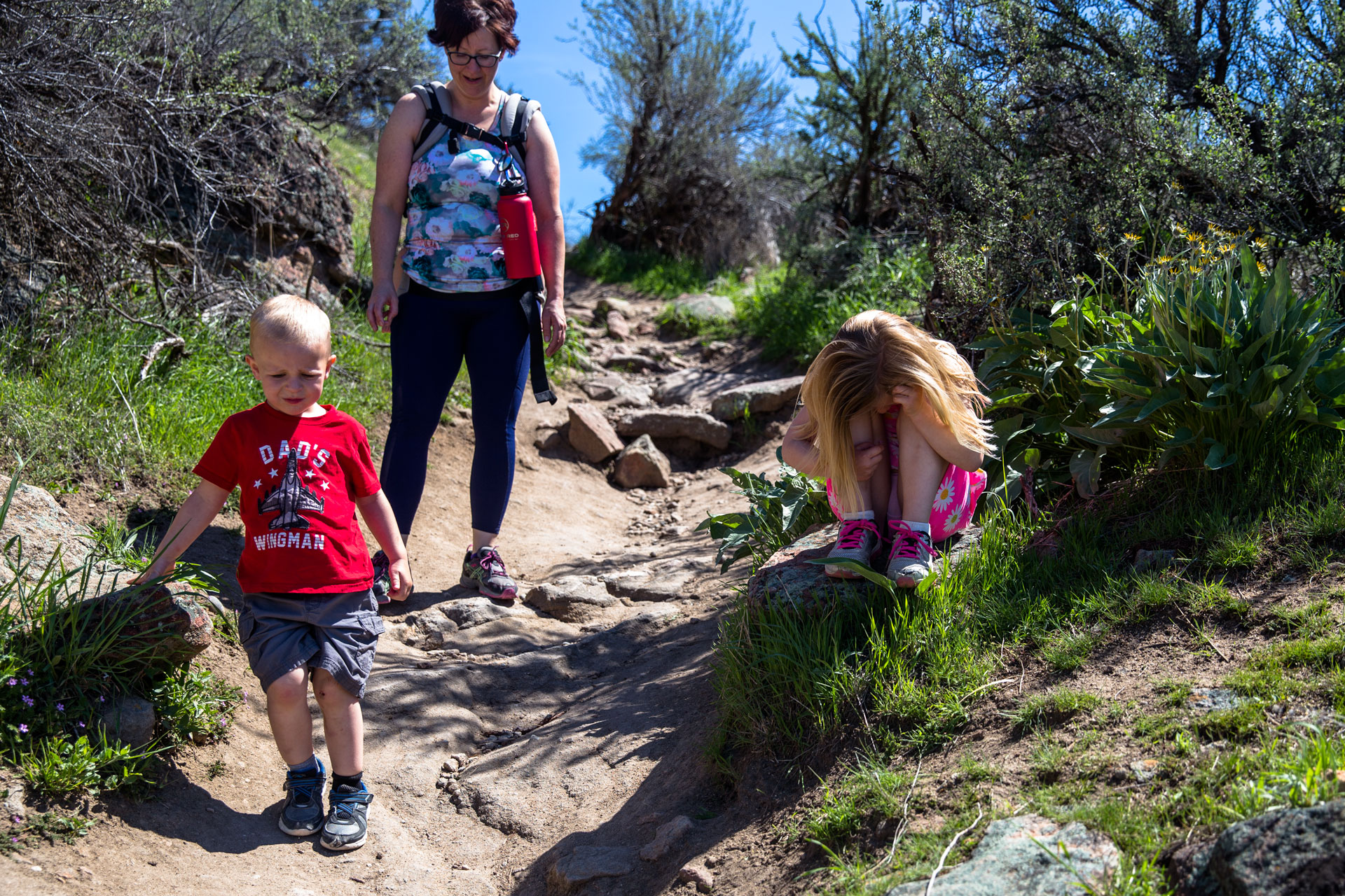 kids and mom traveling down the trail and daughter sitting on a rock with her head between her legs