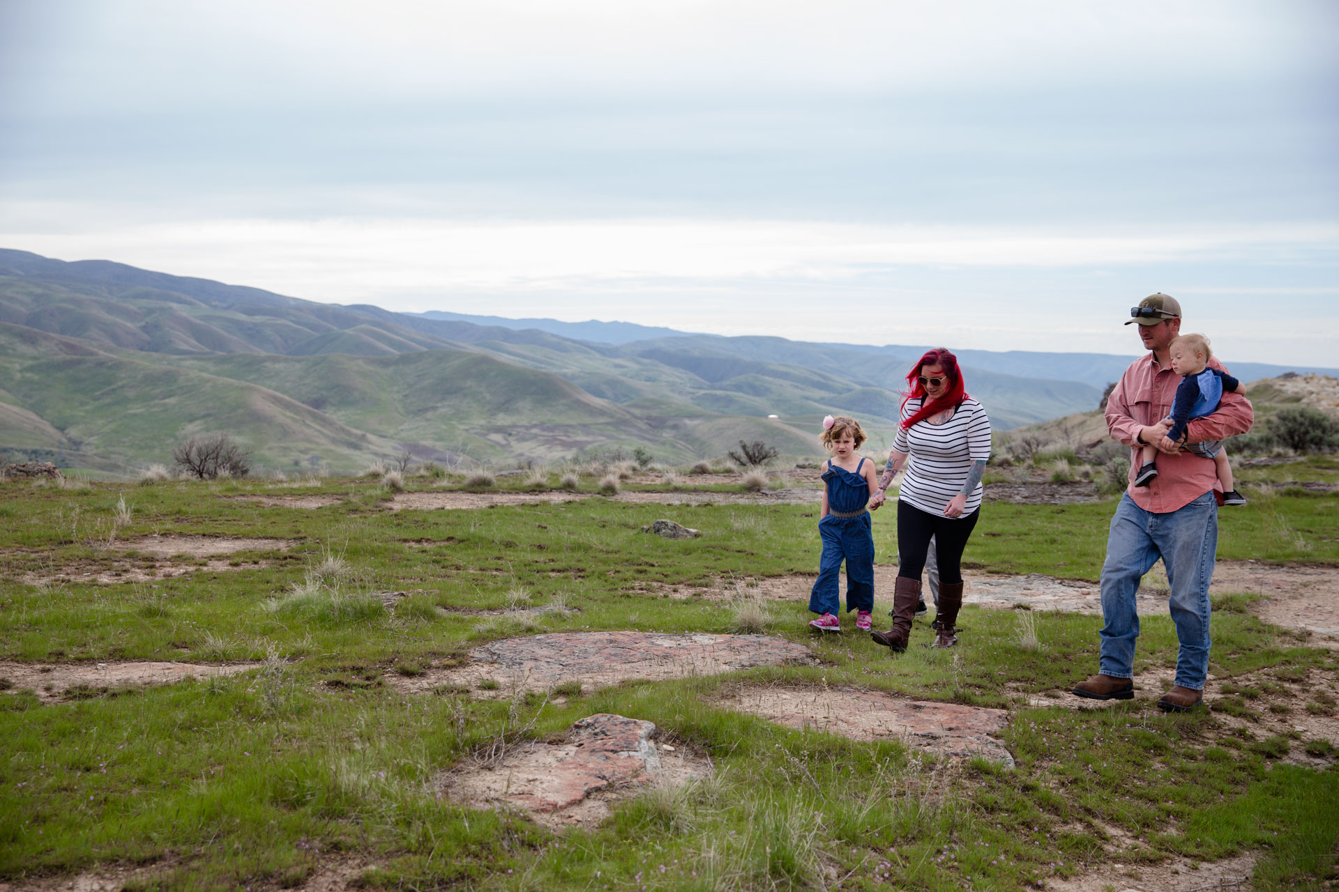 family walking on top of a mountain with the beautiful foothills in the background