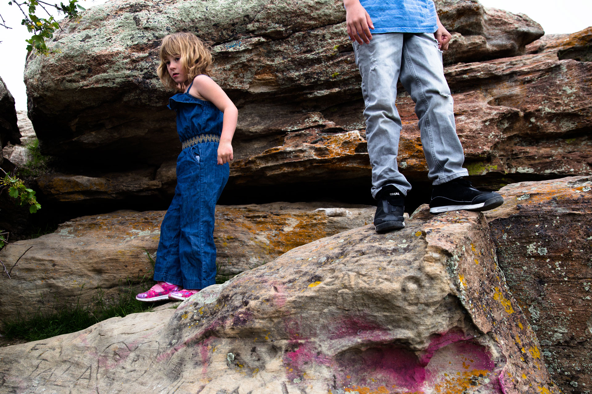 Two kids climbing all over the rocks by themselves