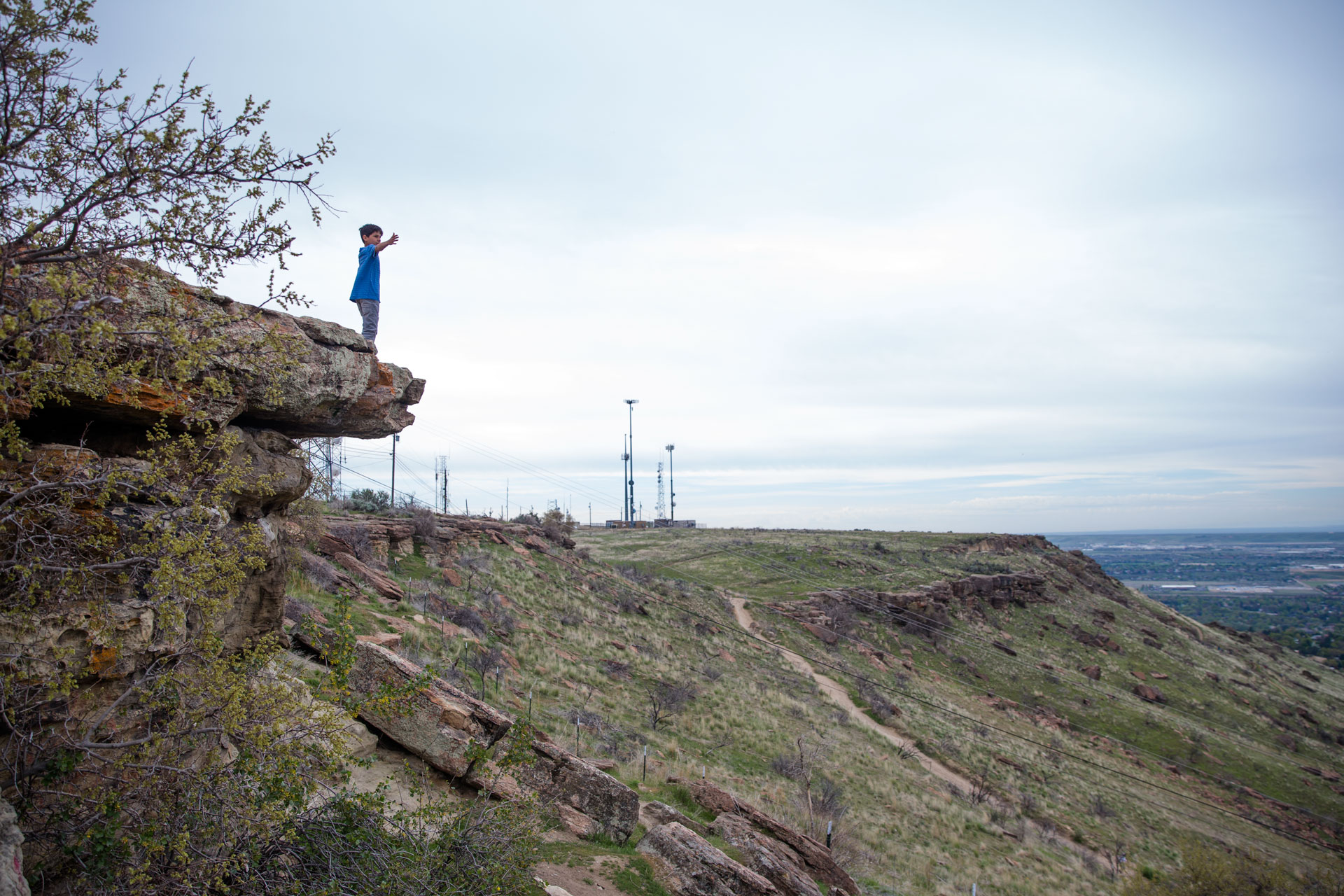 Boy standing on top of the rocks at Table Rock with his arms open wide