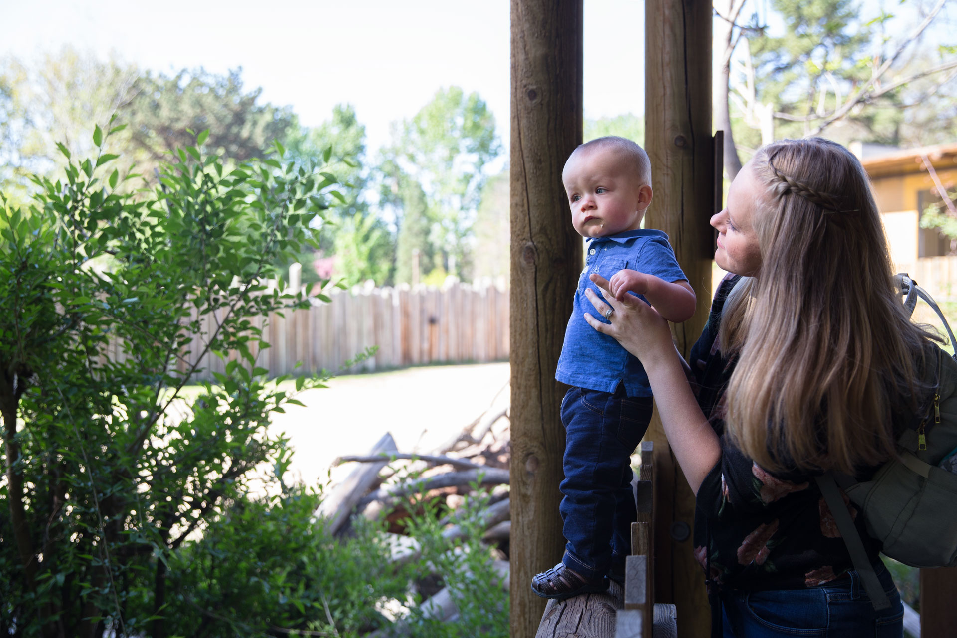 Mom holding toddler son on the fence as they look art the giraffes at the zoo