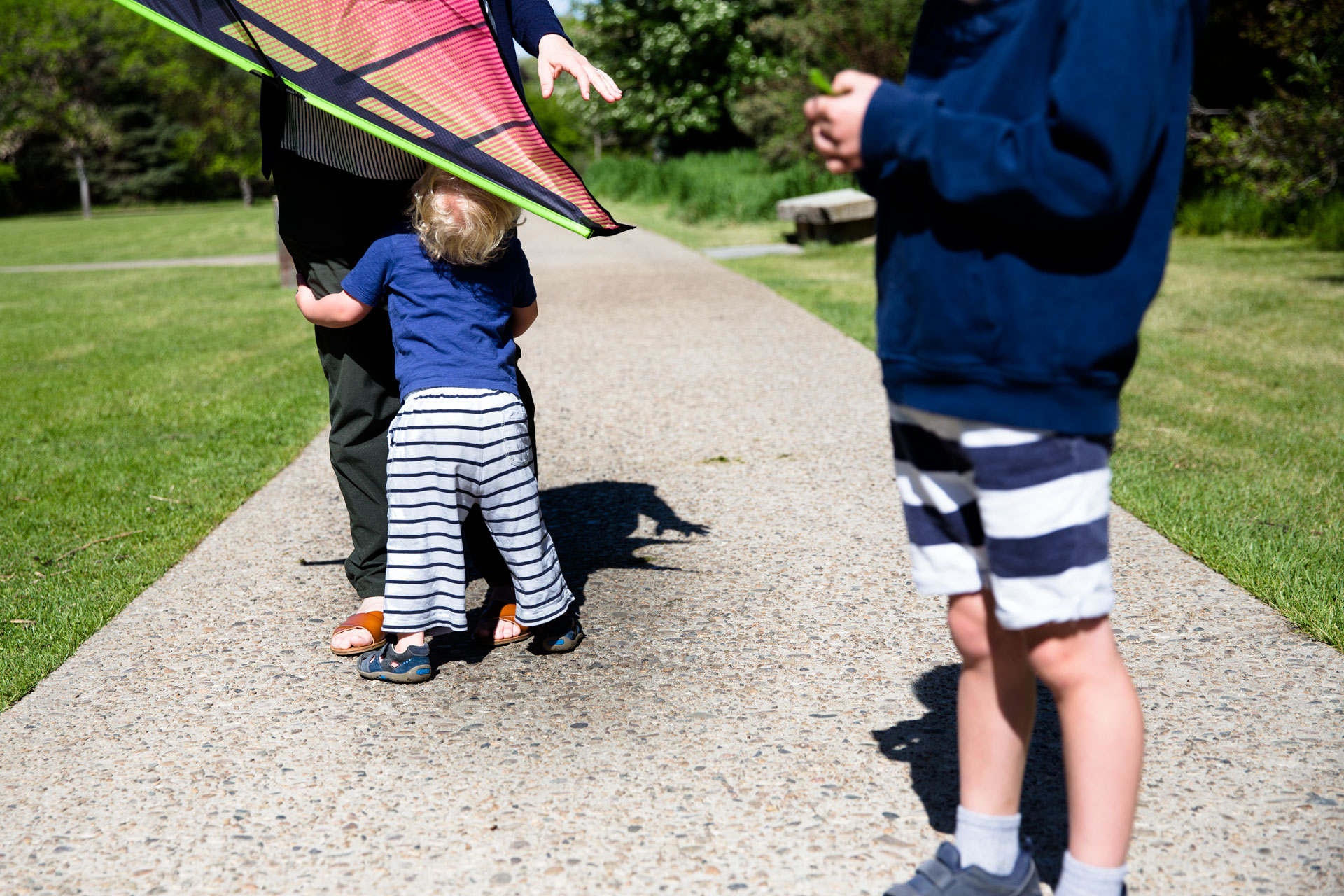 Mom holding kite while little brother looks up at her and older brother plays with his hands to the side