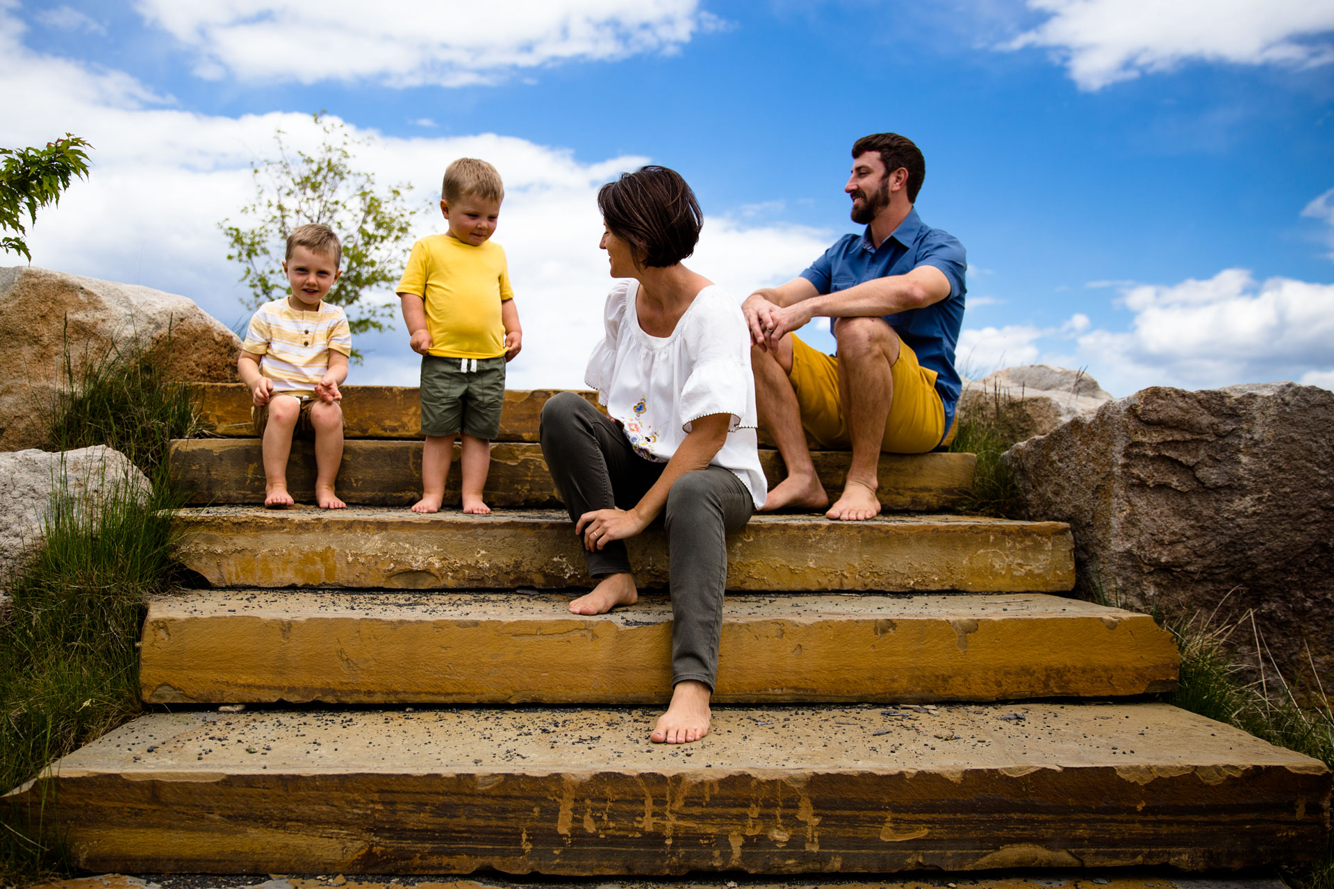 Family of four sitting on stone steps and looking at each other and smiling