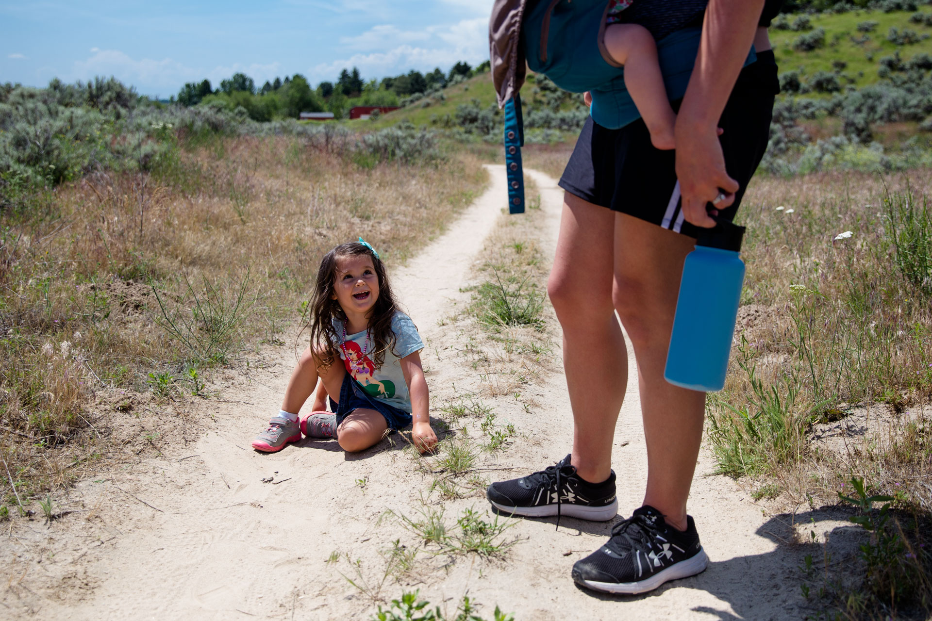 Girl sitting not he ground looking up at mom who is holding her sister in a pack while crying