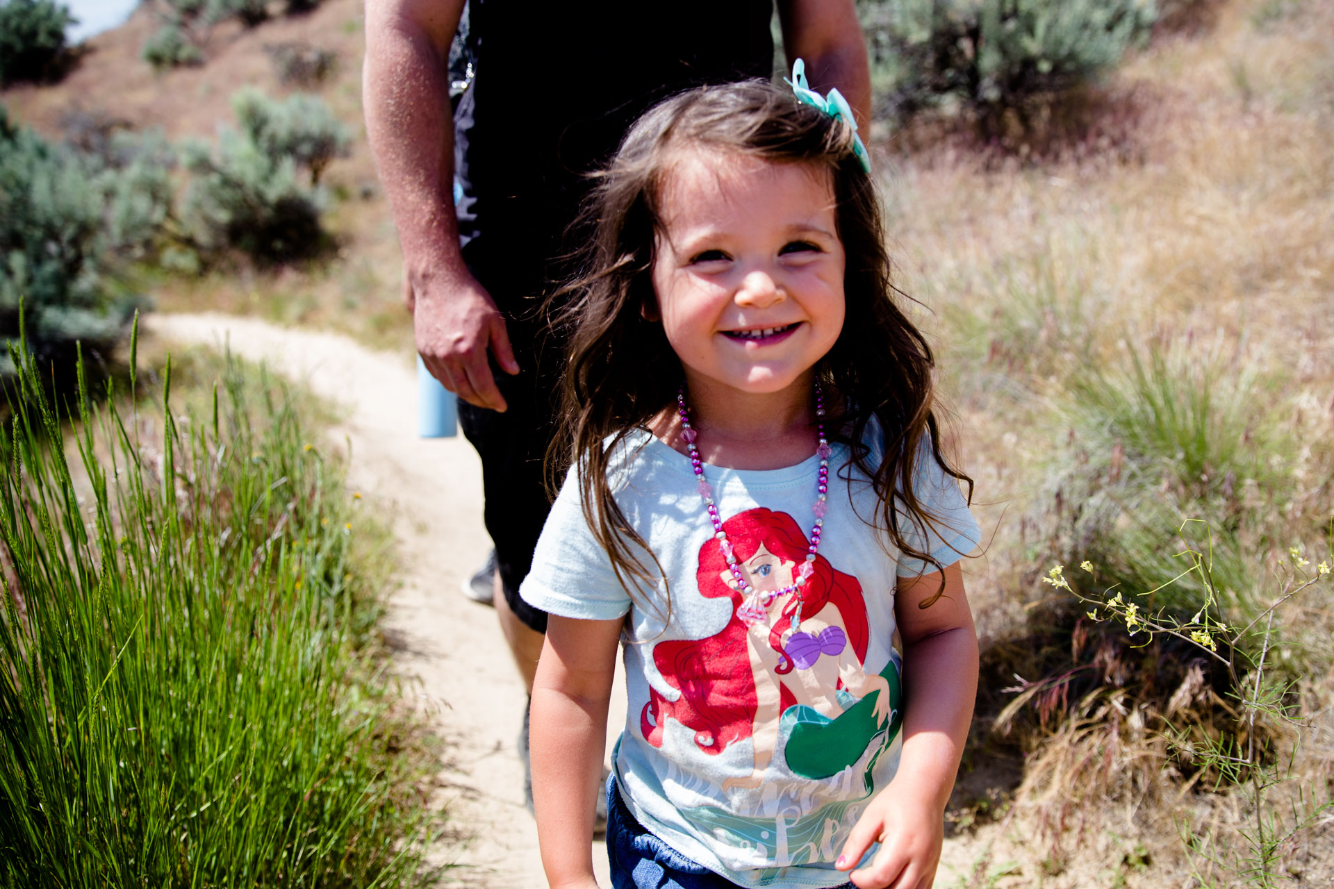Little girl walking down the trail with daddy close behind smiling