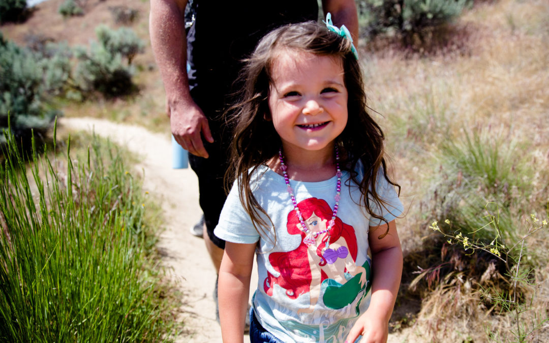 Girl up close and smiling while hiking and dad walking close behind