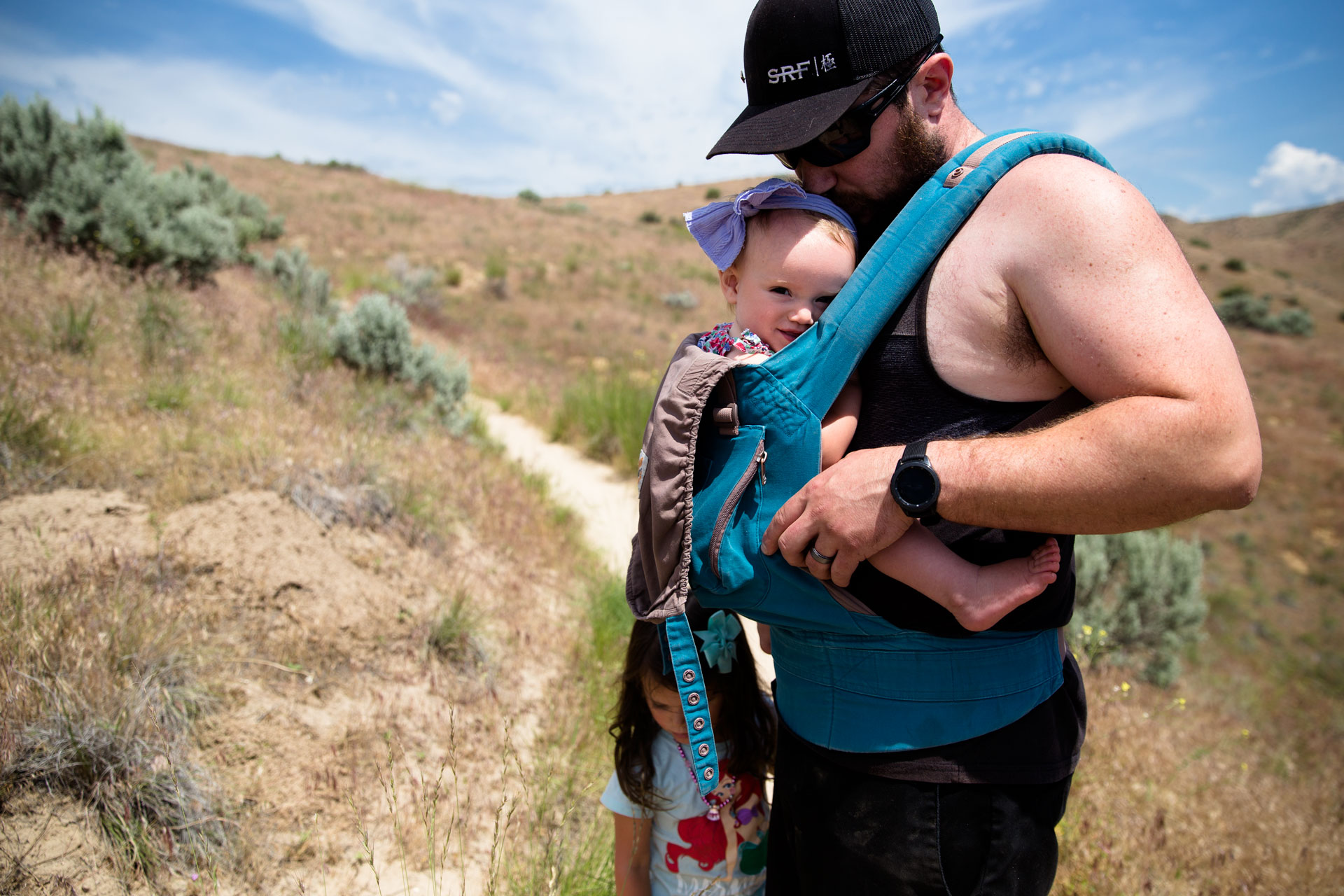 Dad holding infant daughter close to chest and kissing her while hiking in the foothills