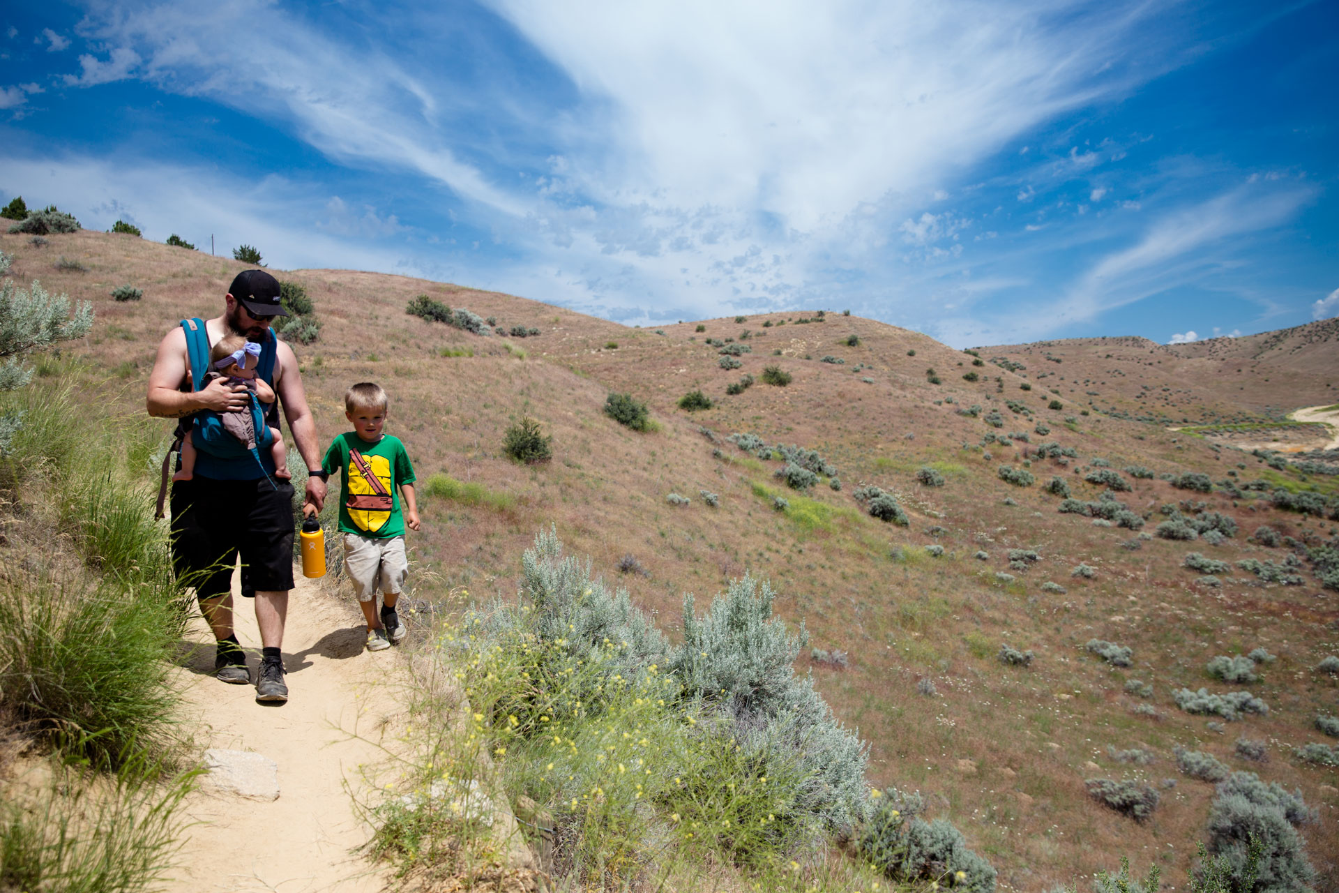 dad holding hands of son while hiking the foothills and holding infant daughter as well