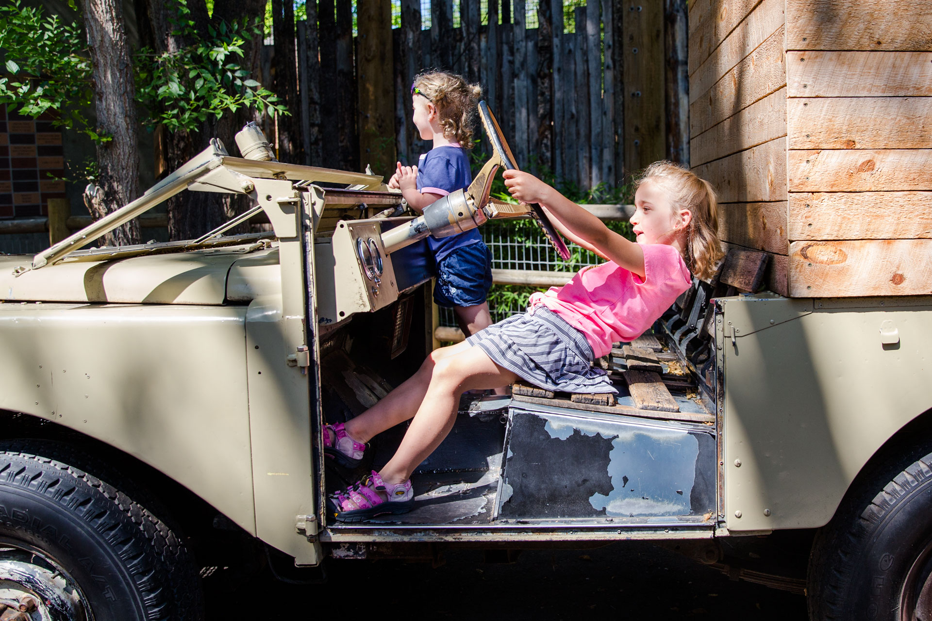Two young girls sitting and playin g in a life-sized pretend jeep at the zoo