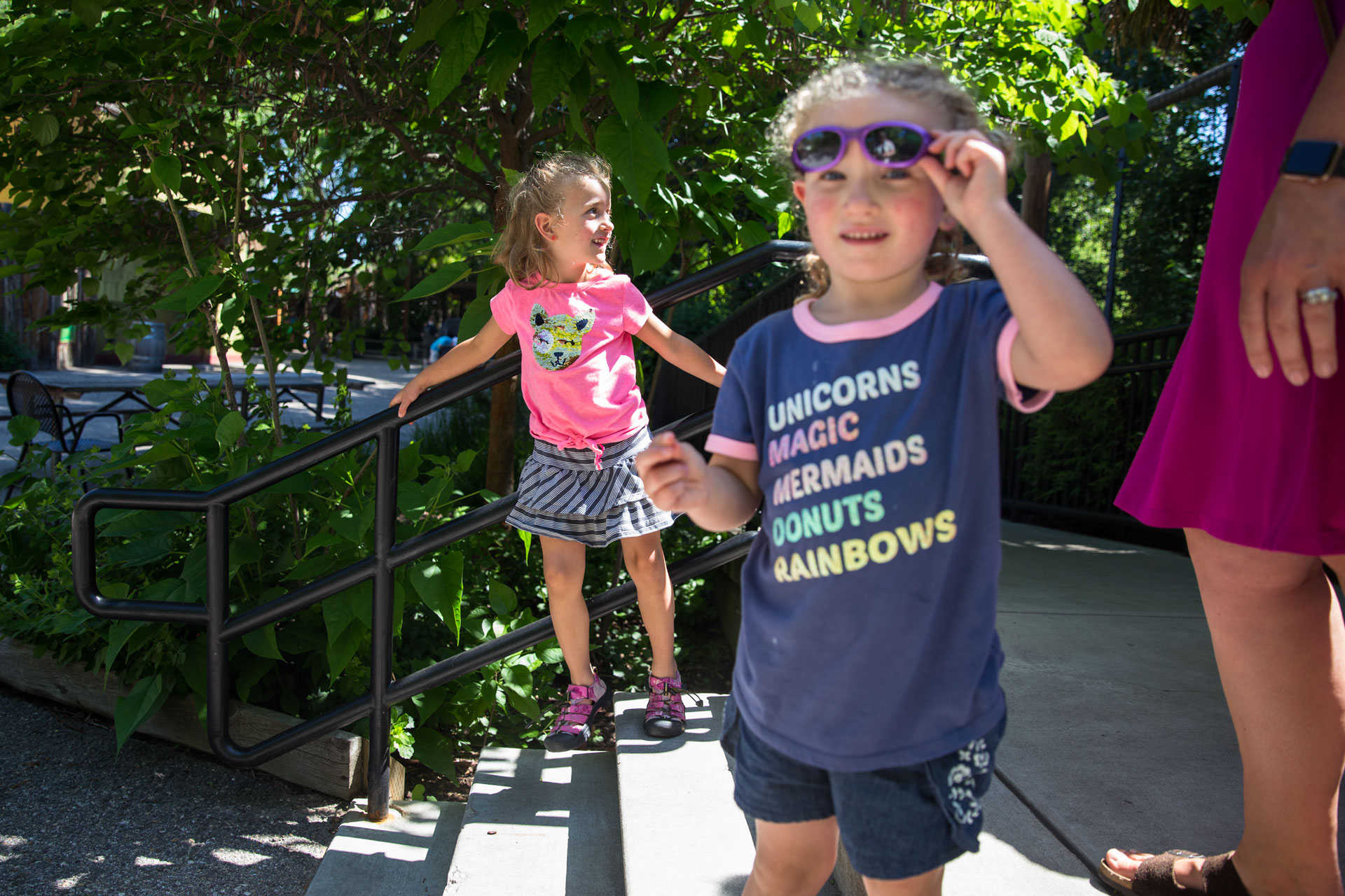 Two young sisters walking down the steps at the zoo and one looking at the camera with her sunglasses raised up
