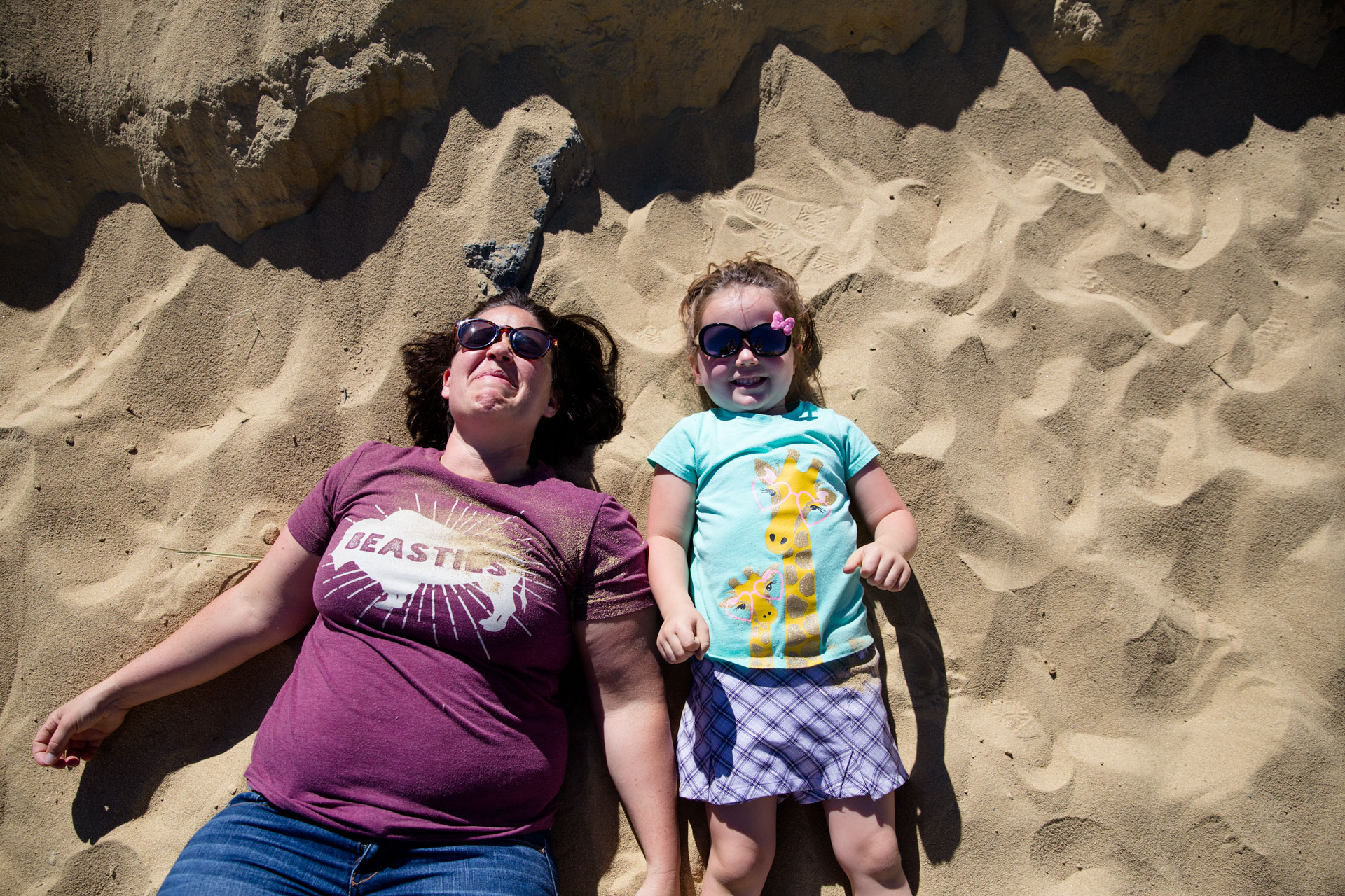 Mom and daughter laying on sand and smiling with sunglasses on