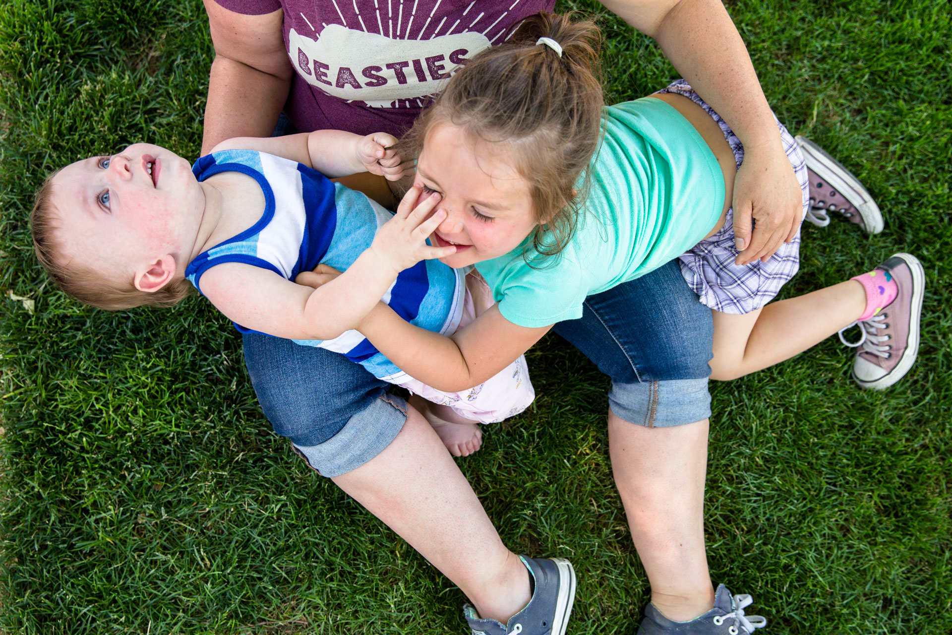 two kids falling over moms legs on the grass laughing