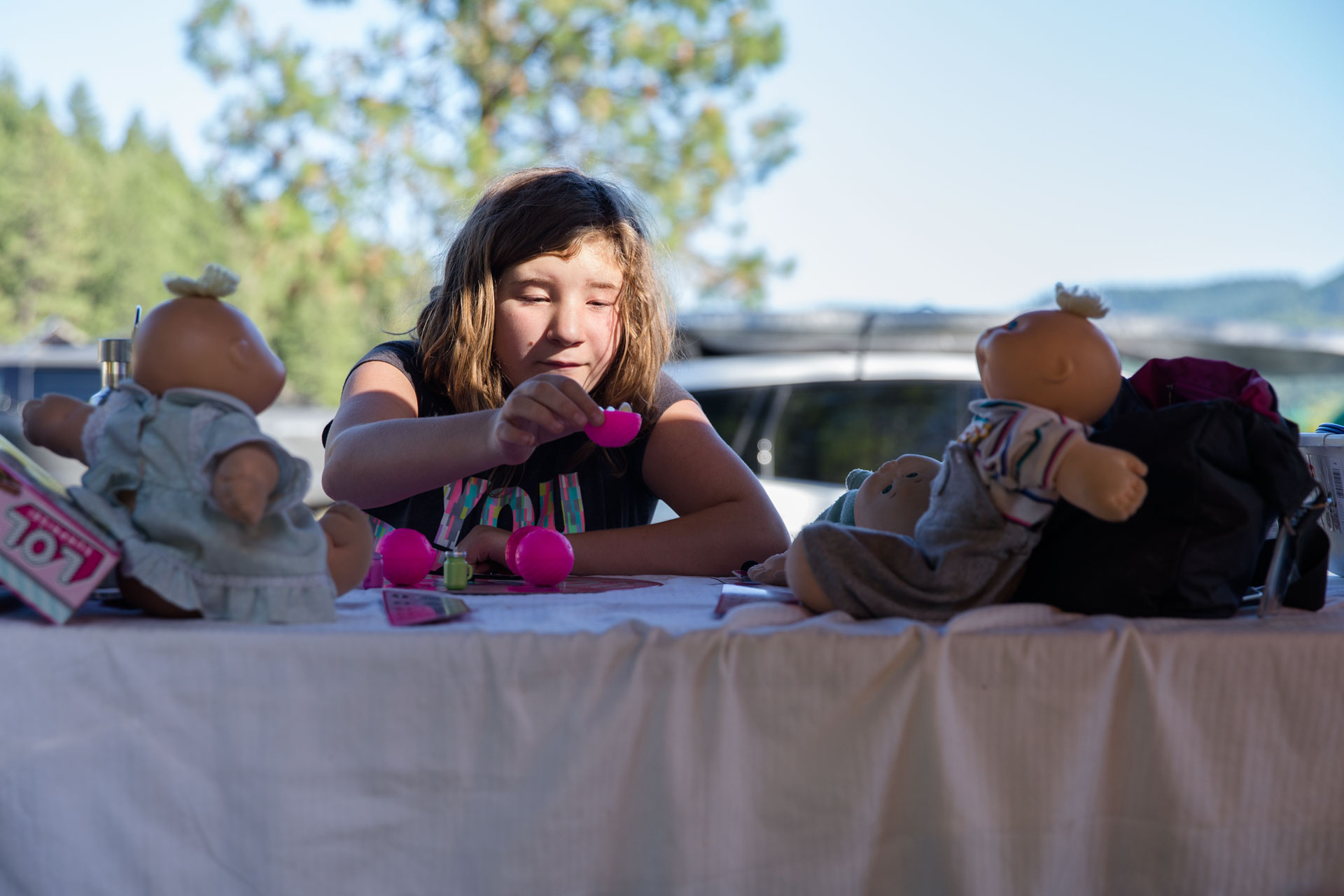 Young girl playing with cabbage patch dolls while camping at the table