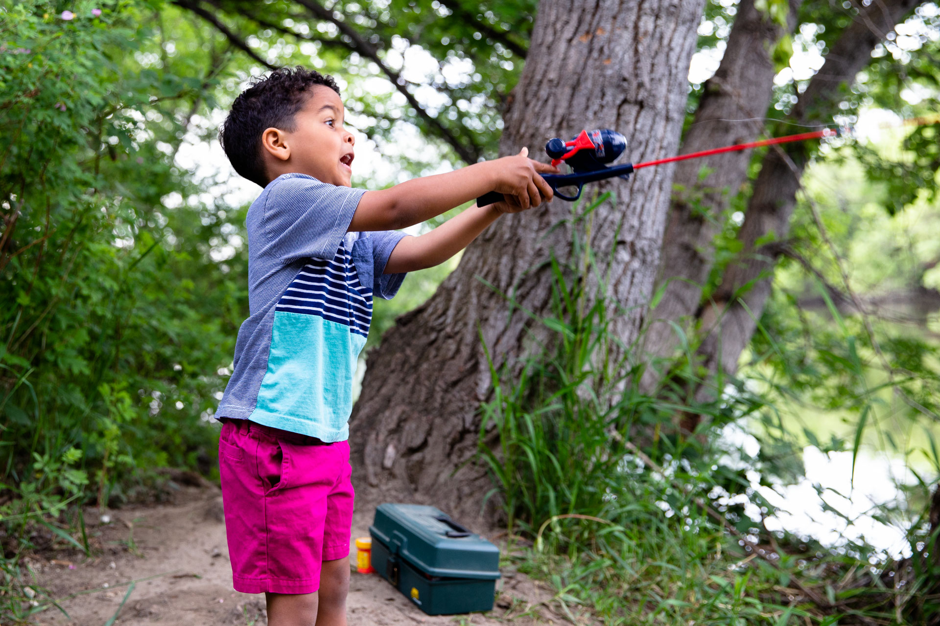 boy casting his fishing line into the river with a wide amazed smile on is face