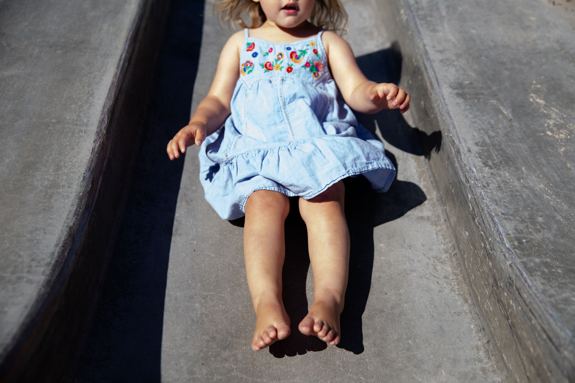 Little girl sliding down a concrete slide