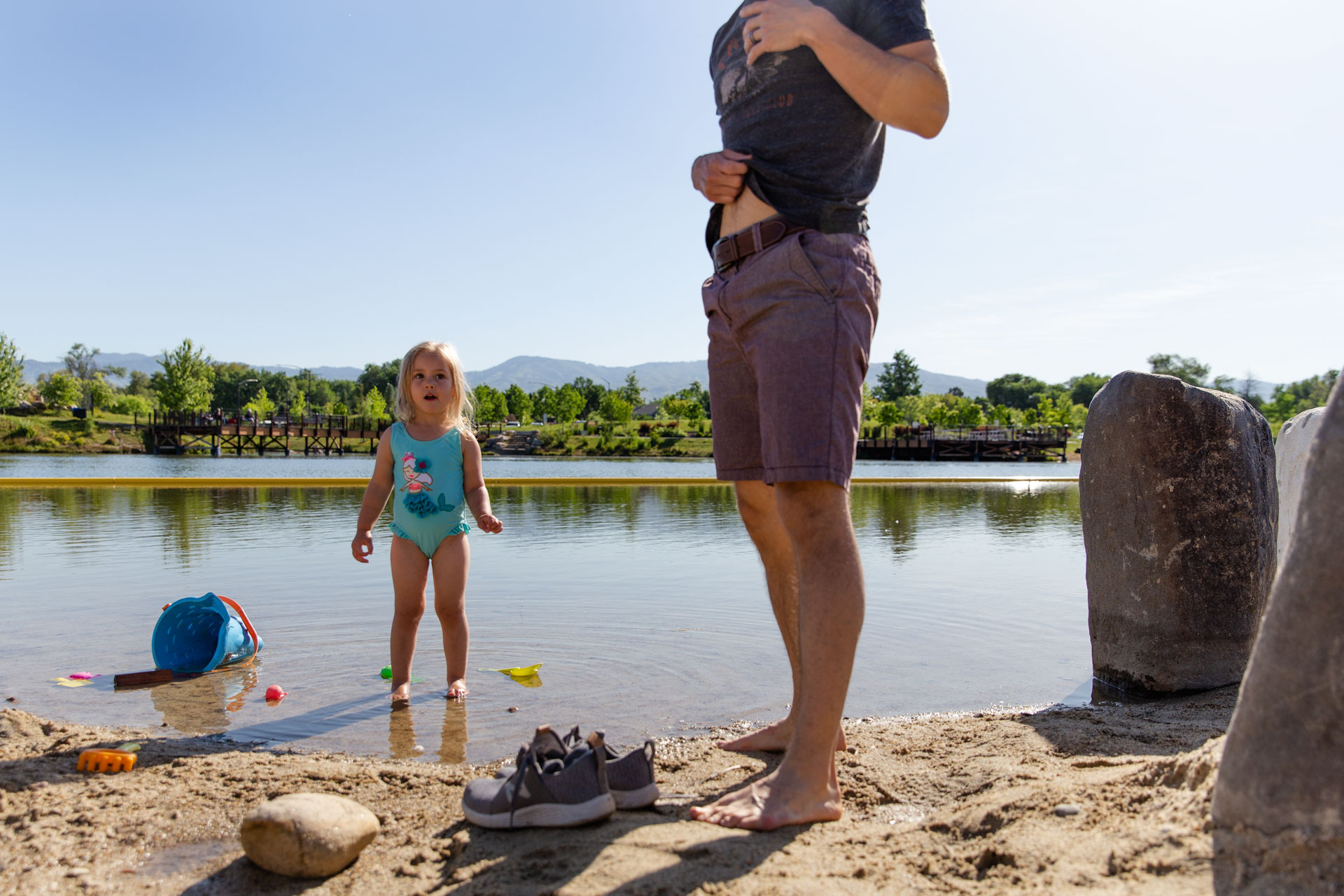 Dad standing up next to daughter with his short up showing his belly and daughter looking at him with an awe face by the lake