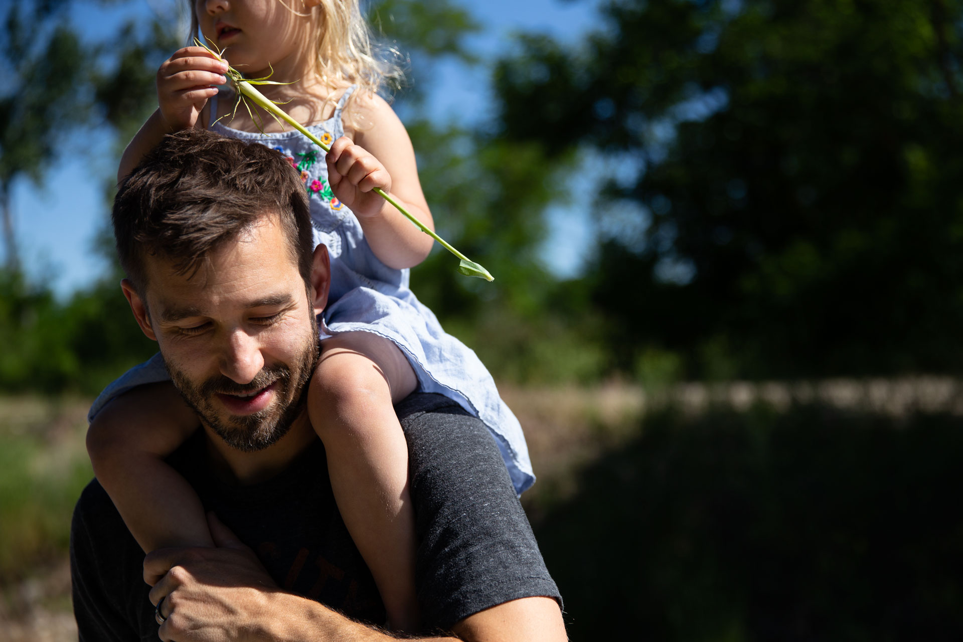 close up of Dad smiling while holding  daughter on his shoulders and she is holding a flower