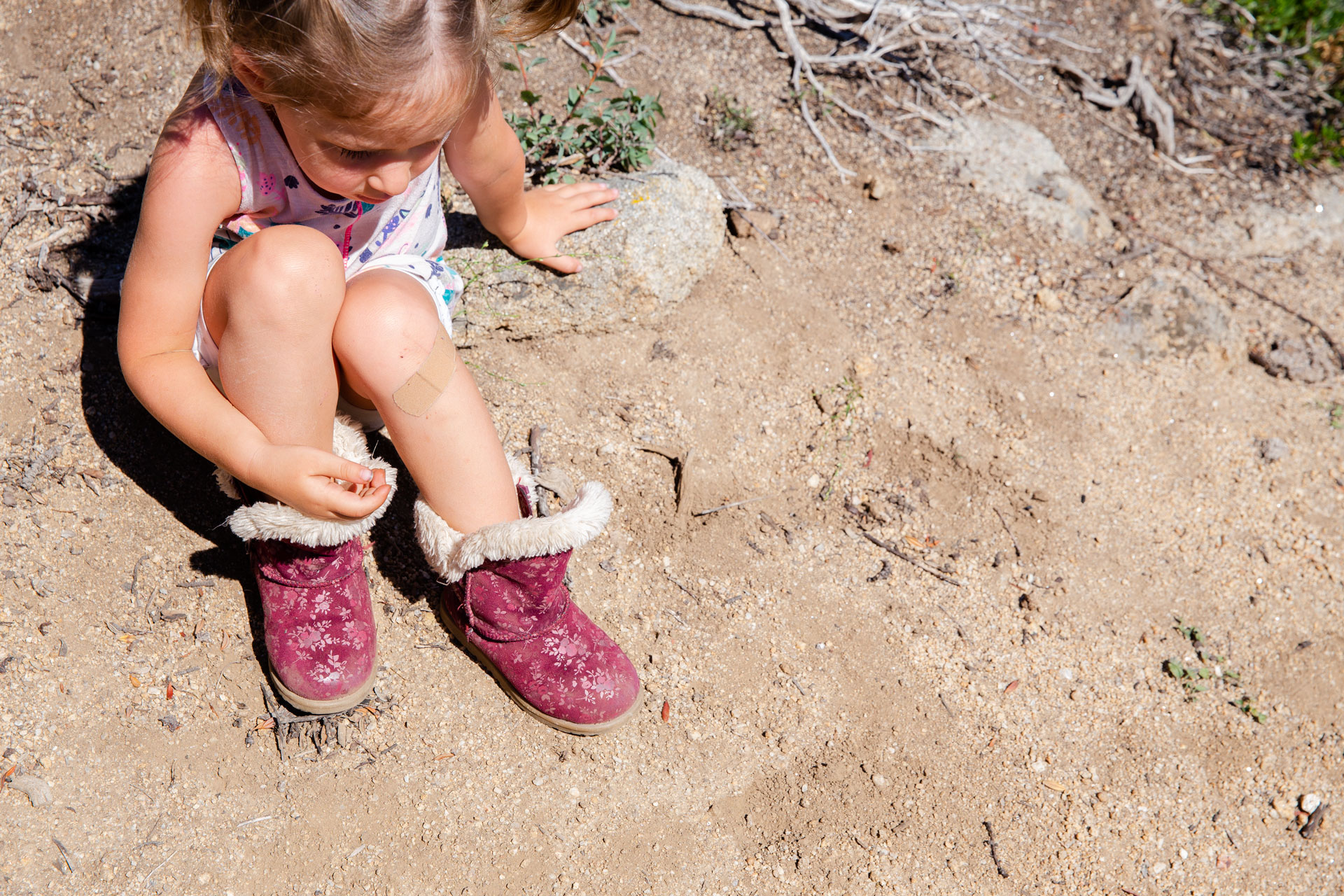 young girl sitting on the dirt holding her legs to her chest and having a bandaid on her knee