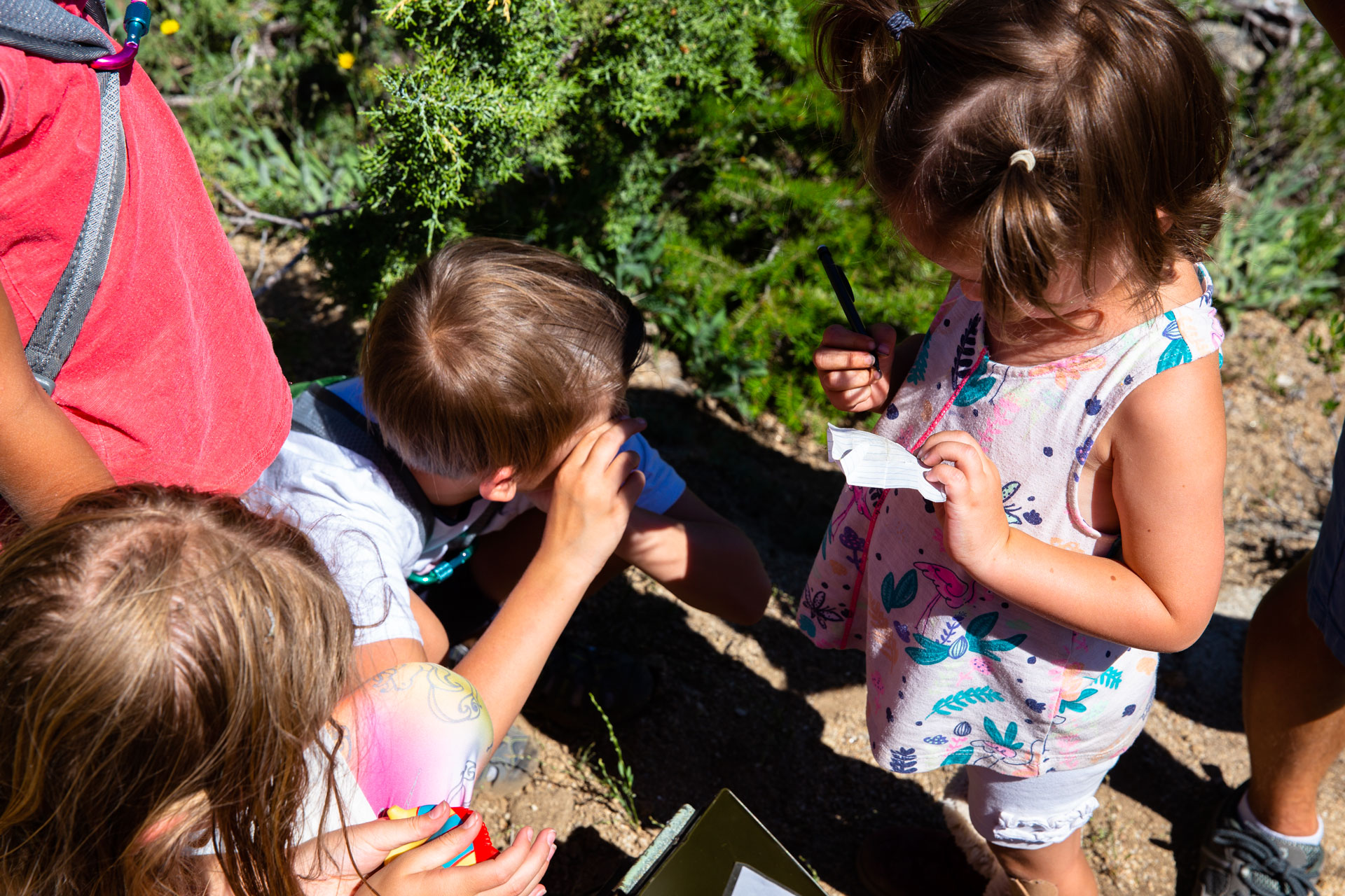 kids looking through a geocache and writing their names on the paper
