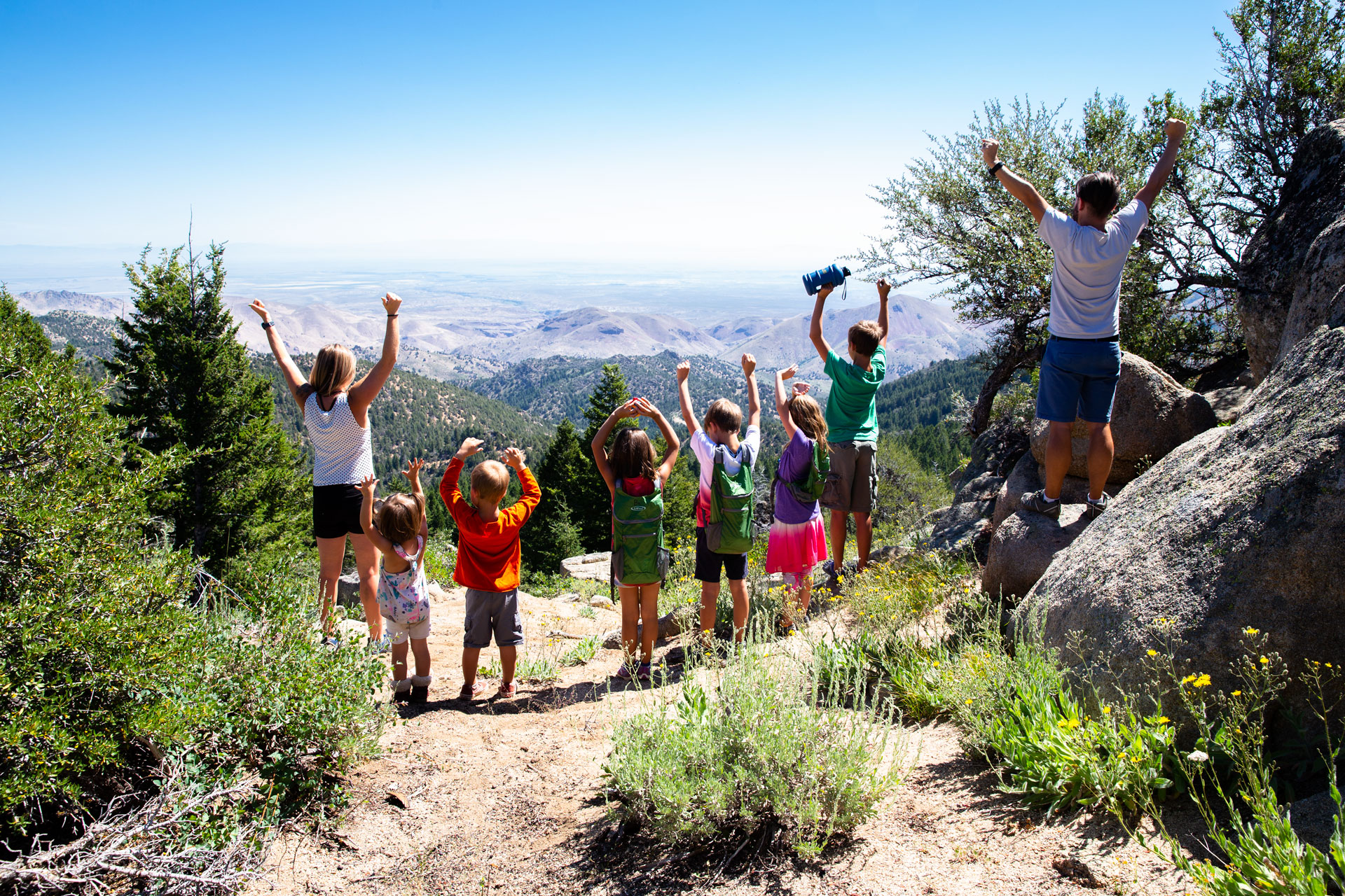 family of 8 cheering as we see them from behind on top of a mountain