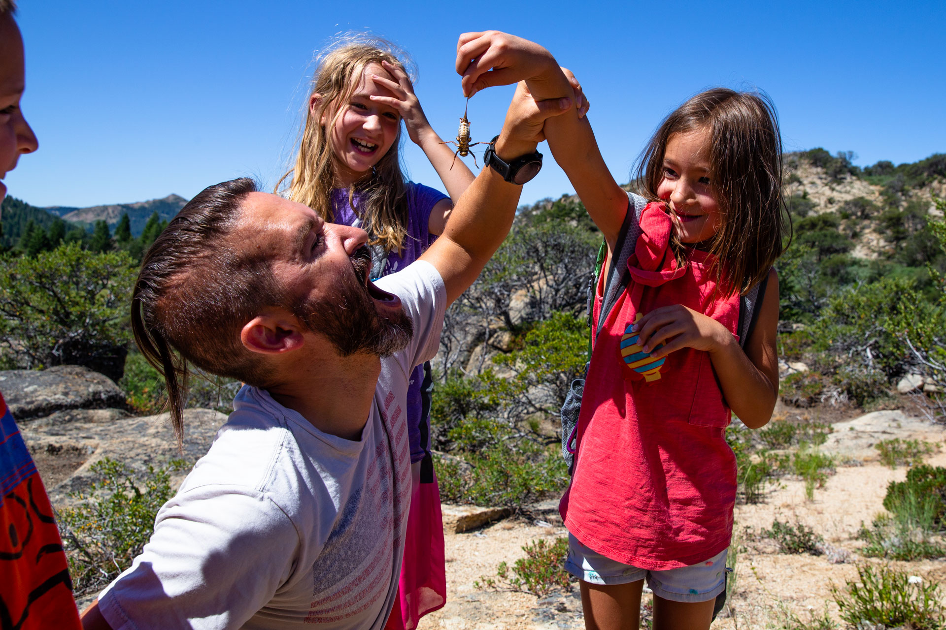 dad pretending to eat a bug while daughter holds int above his head in the mountains